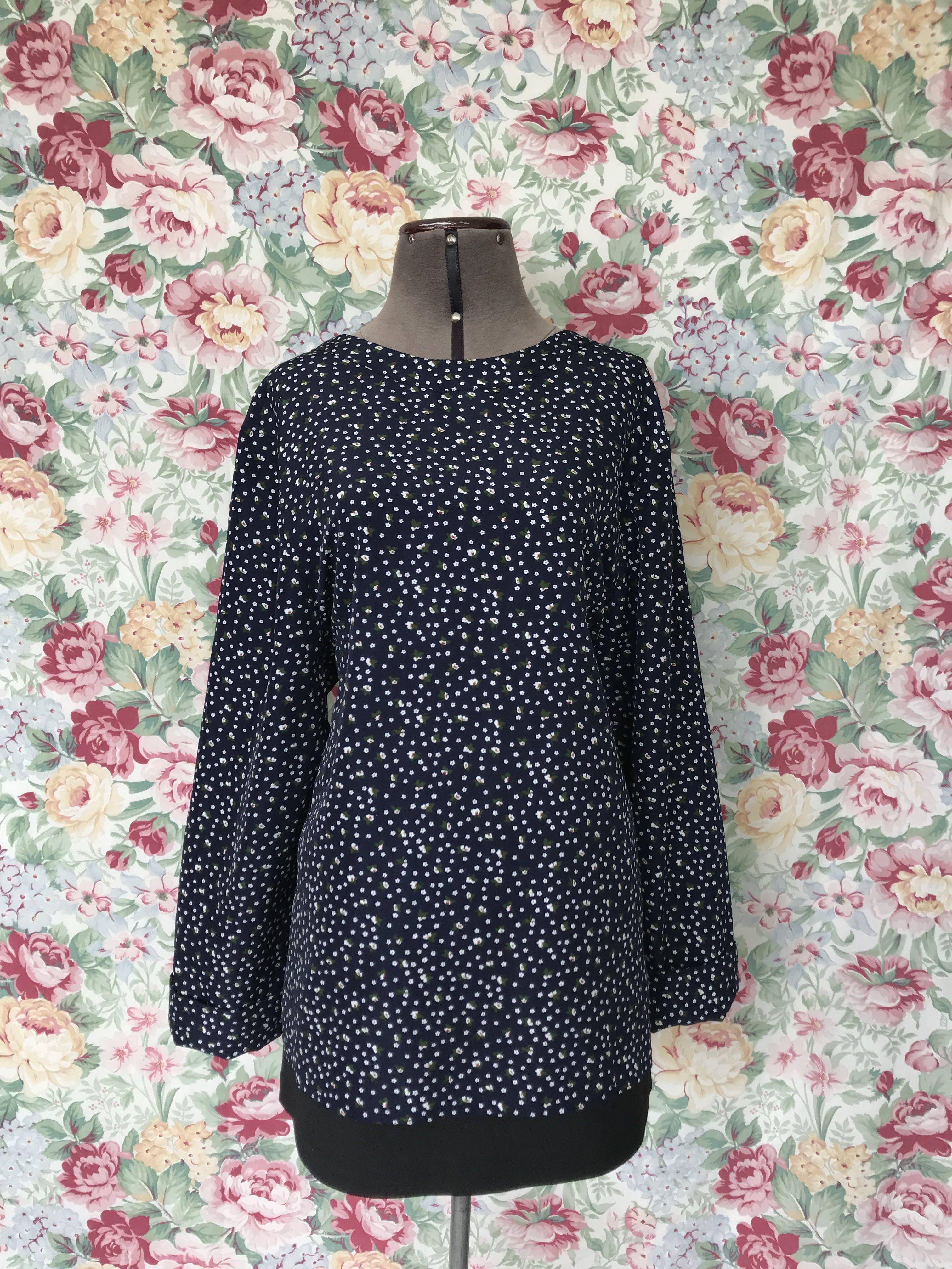 Blusa fondo azul con estampado de florcitas blancas, con botones nacarados en el cuello y doblez en las mangas Talla L