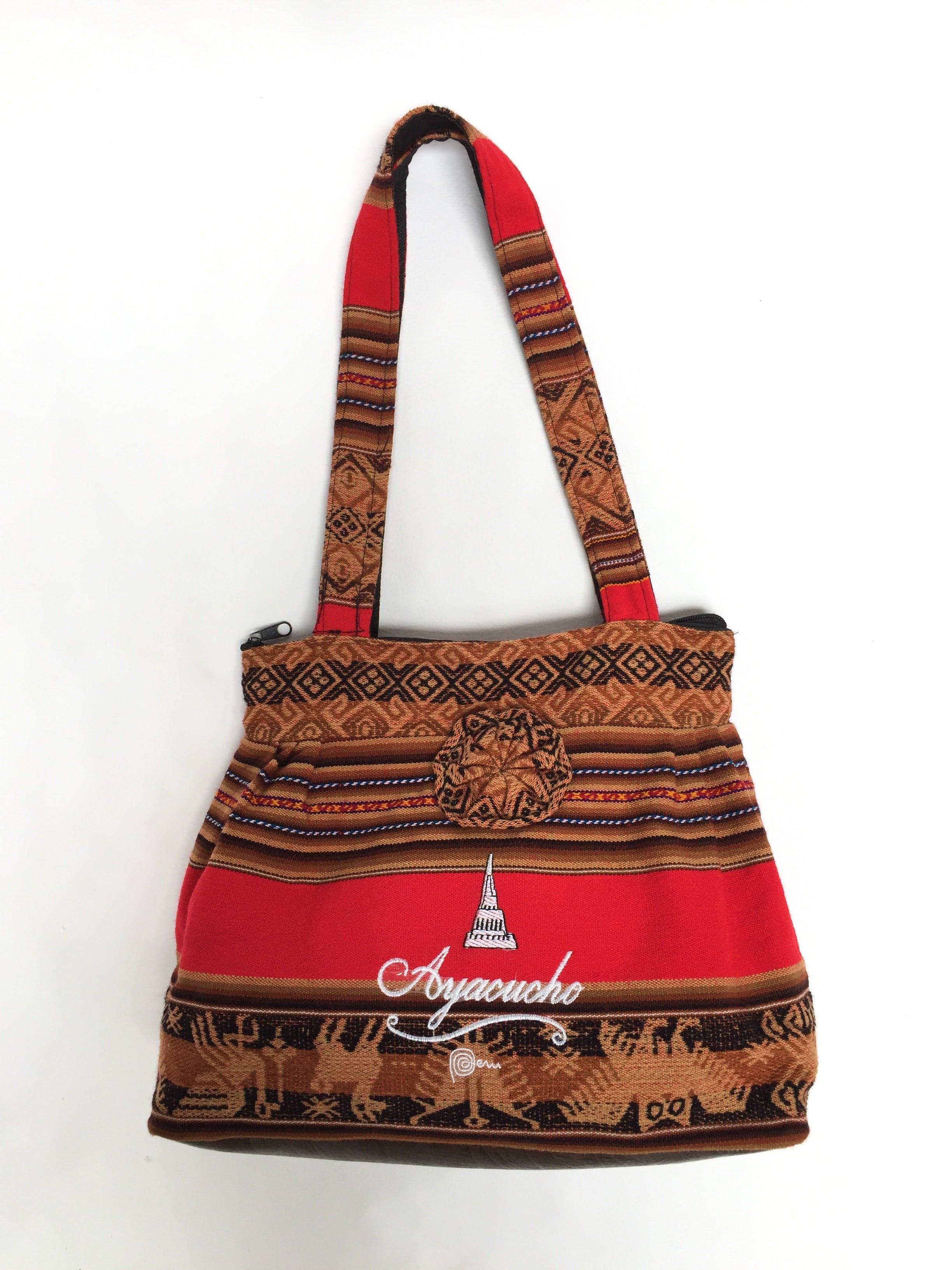 Cartera tejida en tonos marrones, rojos y azules, bordado blanco de Ayacucho, cierre, bolsillo interior, lleva forro y base de cuerina marrón Alto: 27 cm Largo: 42 cm Ancho: 13 cm