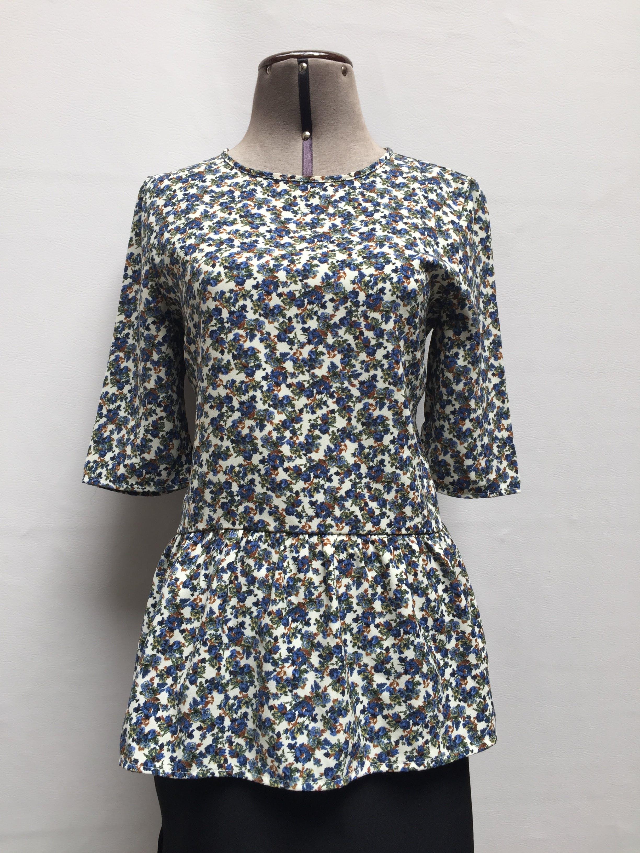 Blusa Zara color crema con florcitas azules, manga 3/4 y volante en la basta. Tiene escote circular en la espalda  Talla M