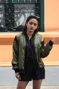 COLECCIÓN UPCYCLING  Rescatada de una pijama estilo seda de hombre. Bomber jacket tela verde olivo satinado con estampado barroco negro, bolsillo original en el pecho, pretinas negras y cierre delantero Talla L foto 1