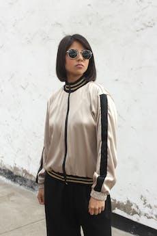 COLECCIÓN UPCYCLING De una falda usada en un matrimonio especial nace esta Bomber jacket con aires de glamour.   Tela con caída, dorada satinada con franjas negras, cierre delantero, pretina, cuello y puños negros con líneas doradas. Talla S-M foto 1