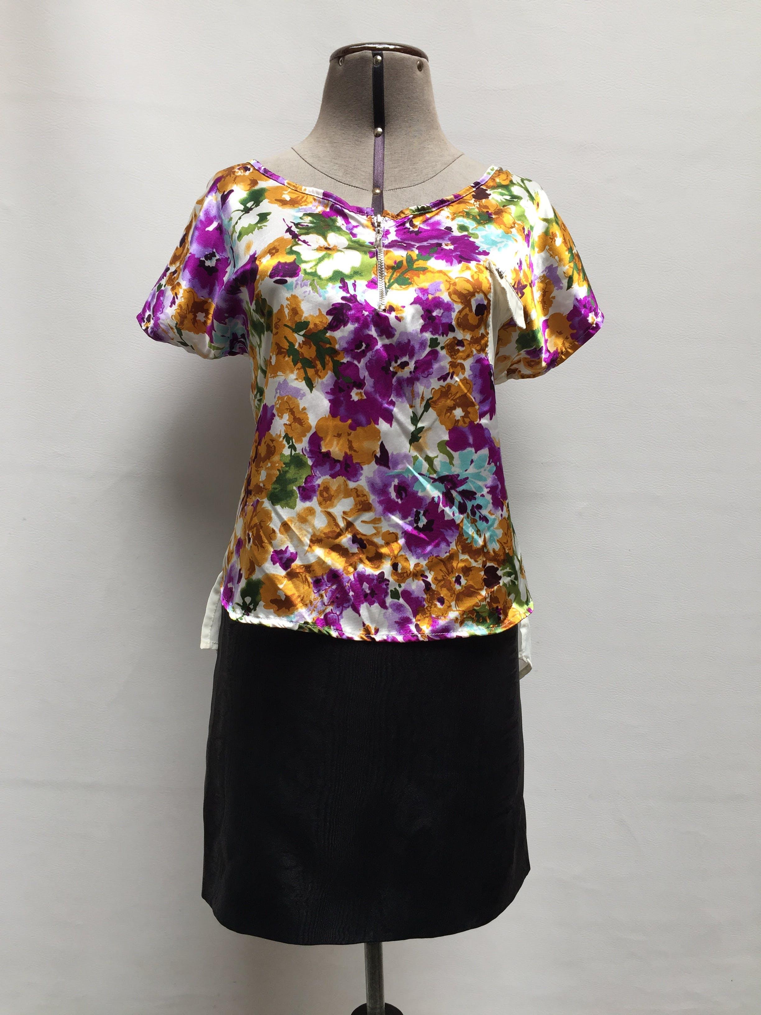 Blusa blanca satinada con estampado de flores en tonos violetas, celestes, amarillas y verdes, parte posterior de gasa blanca, cierre metálico en el escote y bolsillo en el pecho Talla M