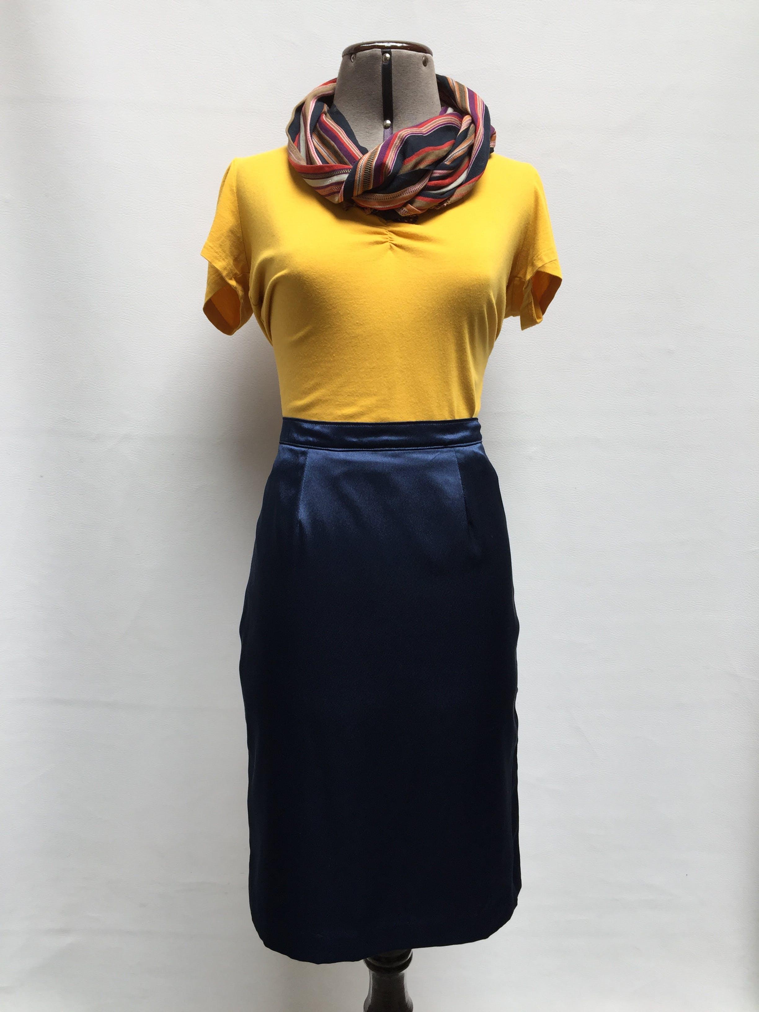 Falda satinada azul, corte recto a la rodilla, con abertura posterior y forro. Talla M