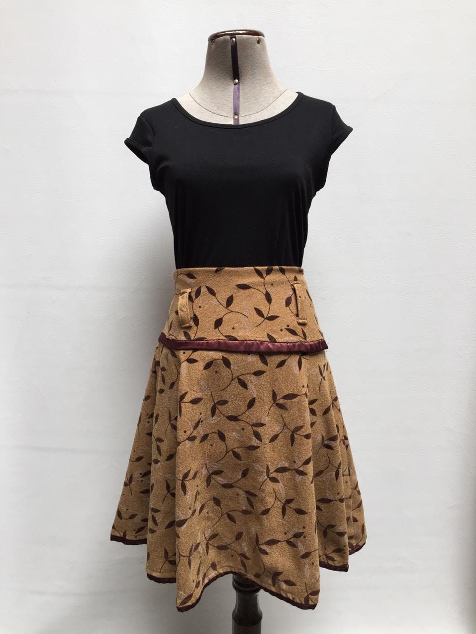 Falda campana tipo tejido en tono camel con estampado de flores, pretina ancha, cierre lateral y franja en la basta Talla M