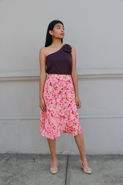 Falda midi de fondo rosa con flores ilustradas y  volantes en la basta, forrada  Talla L
