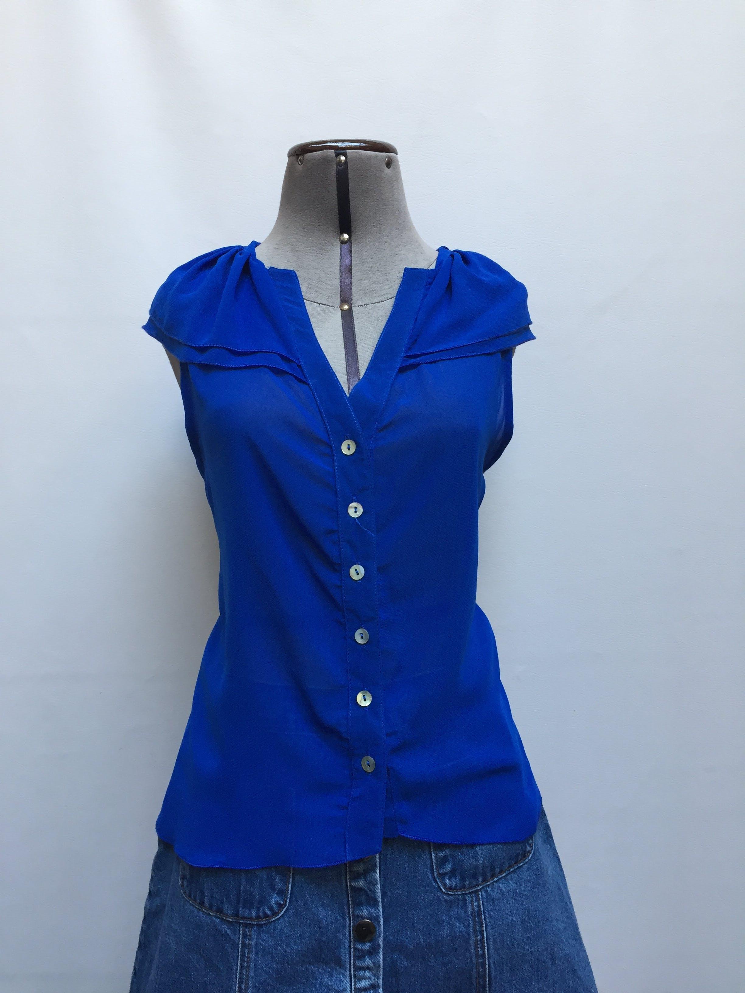Blusa de gasa azul con volante en el cuello, botones delanteros y basta asimétrica Talla M