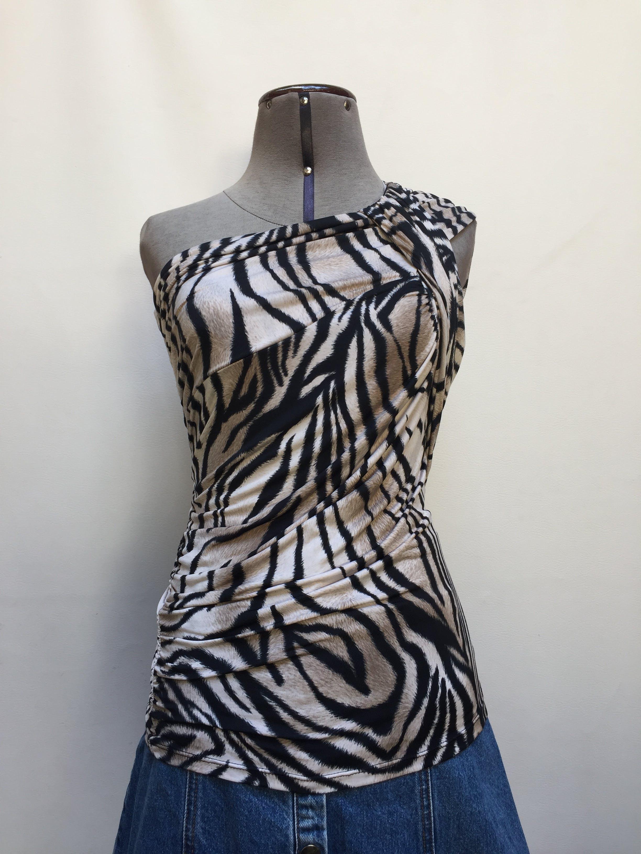 Blusa one shoulder con estampado animal print, tela tipo lycra, corrugado en el hombro con tira para amarrar Talla S