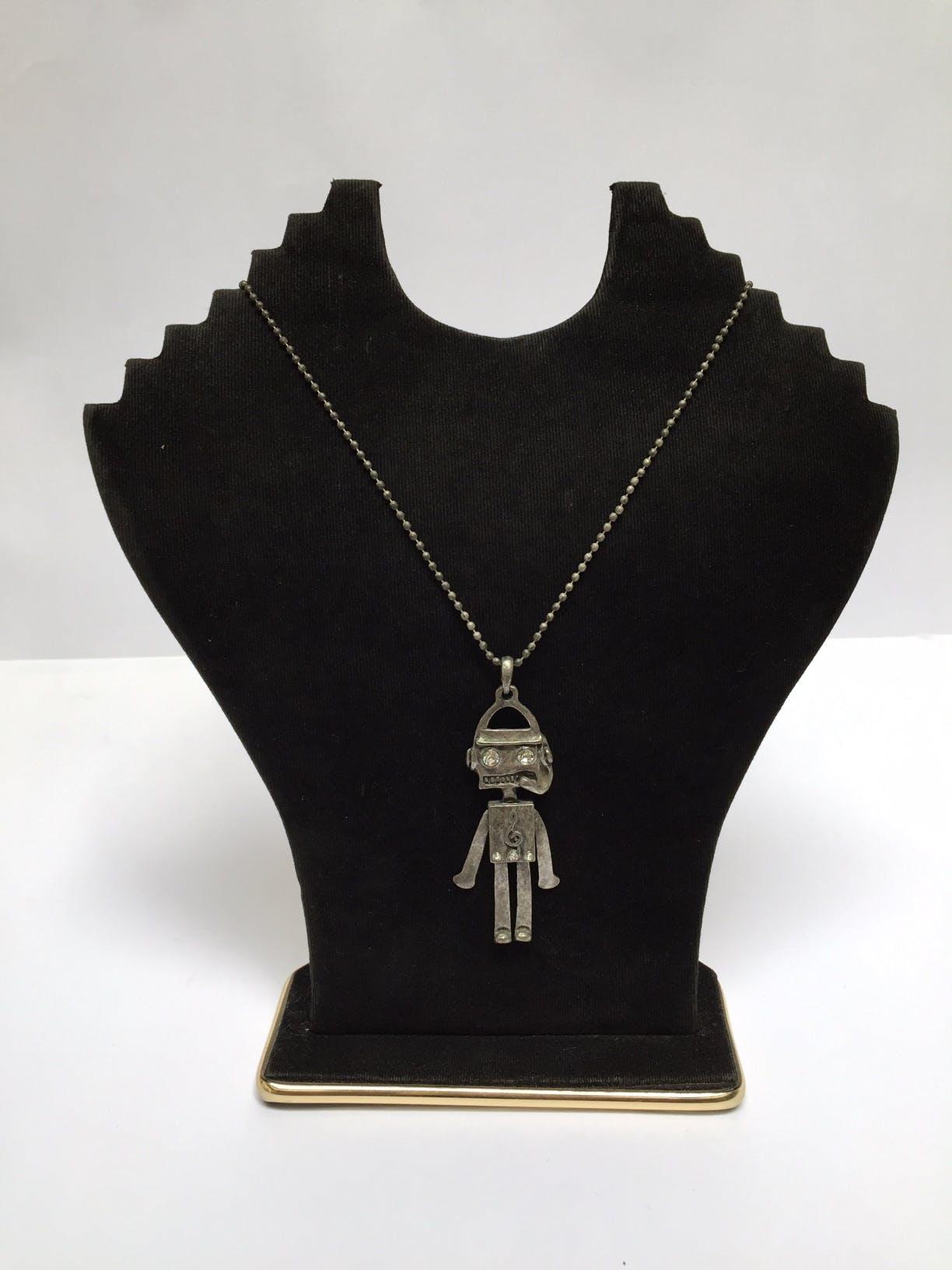 Collar de bolitas plateadas con dije de robot con detalles de incrustaciones tipo diamante en los ojos y pecho Circunferencia: 68 cm Largo de dije: 6,5 cm