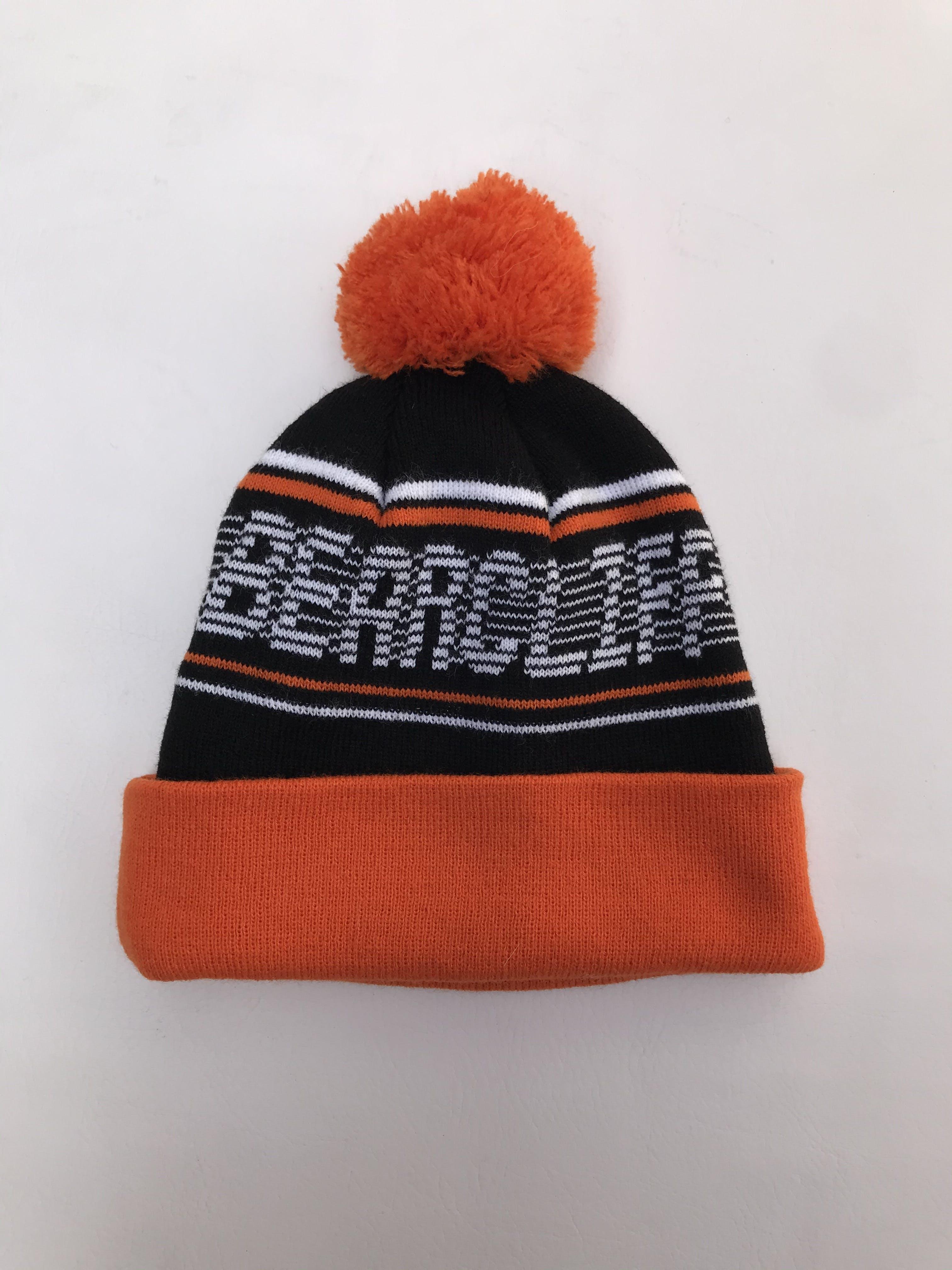 Beanie negro con detalles blancos y anaranjados, pompom y doblez en basta