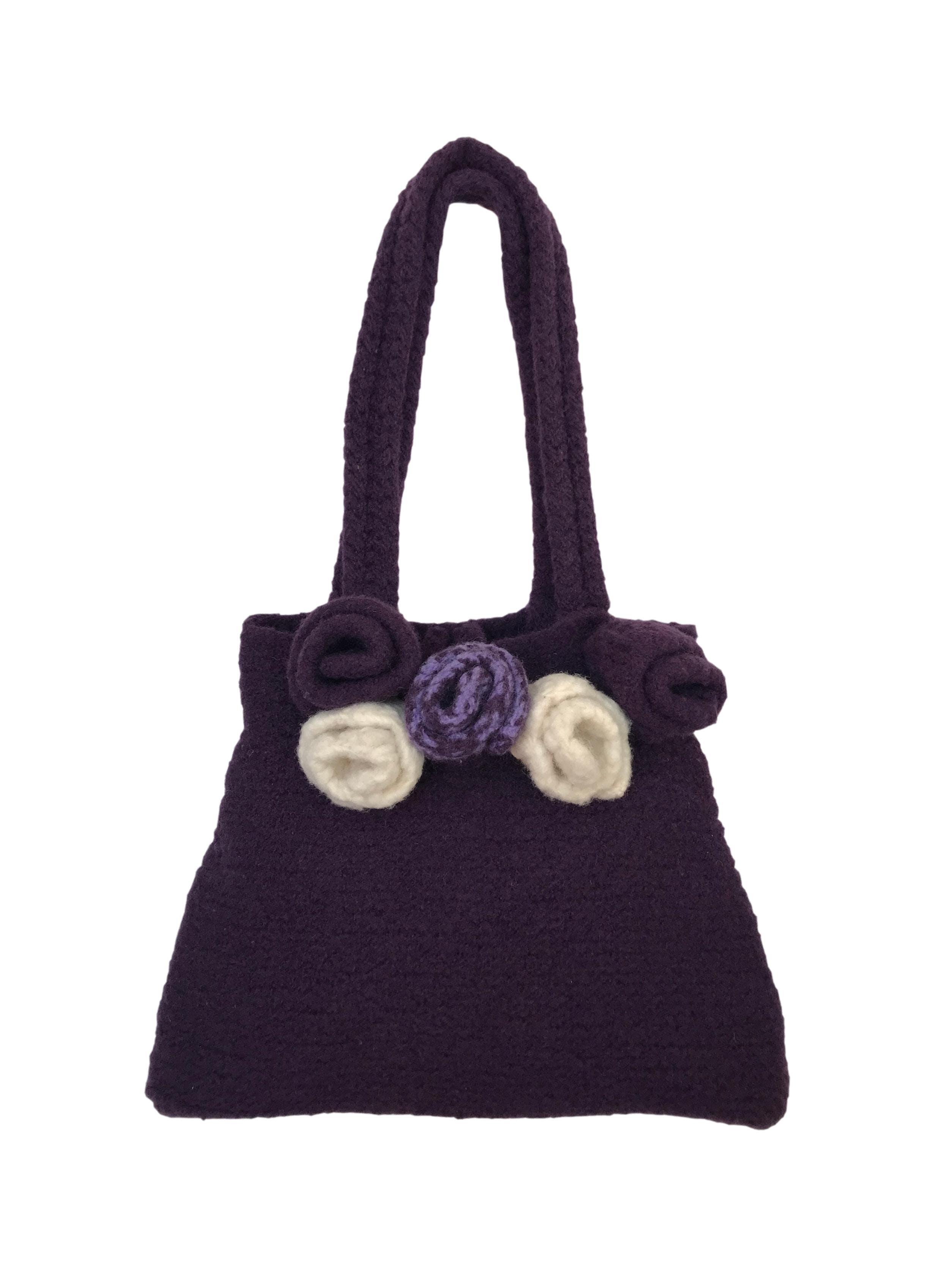 Cartera 100% lana morada con aplicaciones de flores, es forrada, compartimento con cierre interno y doble asa. Alto: 23 cmLargo: 30 cmAncho: 7 cm