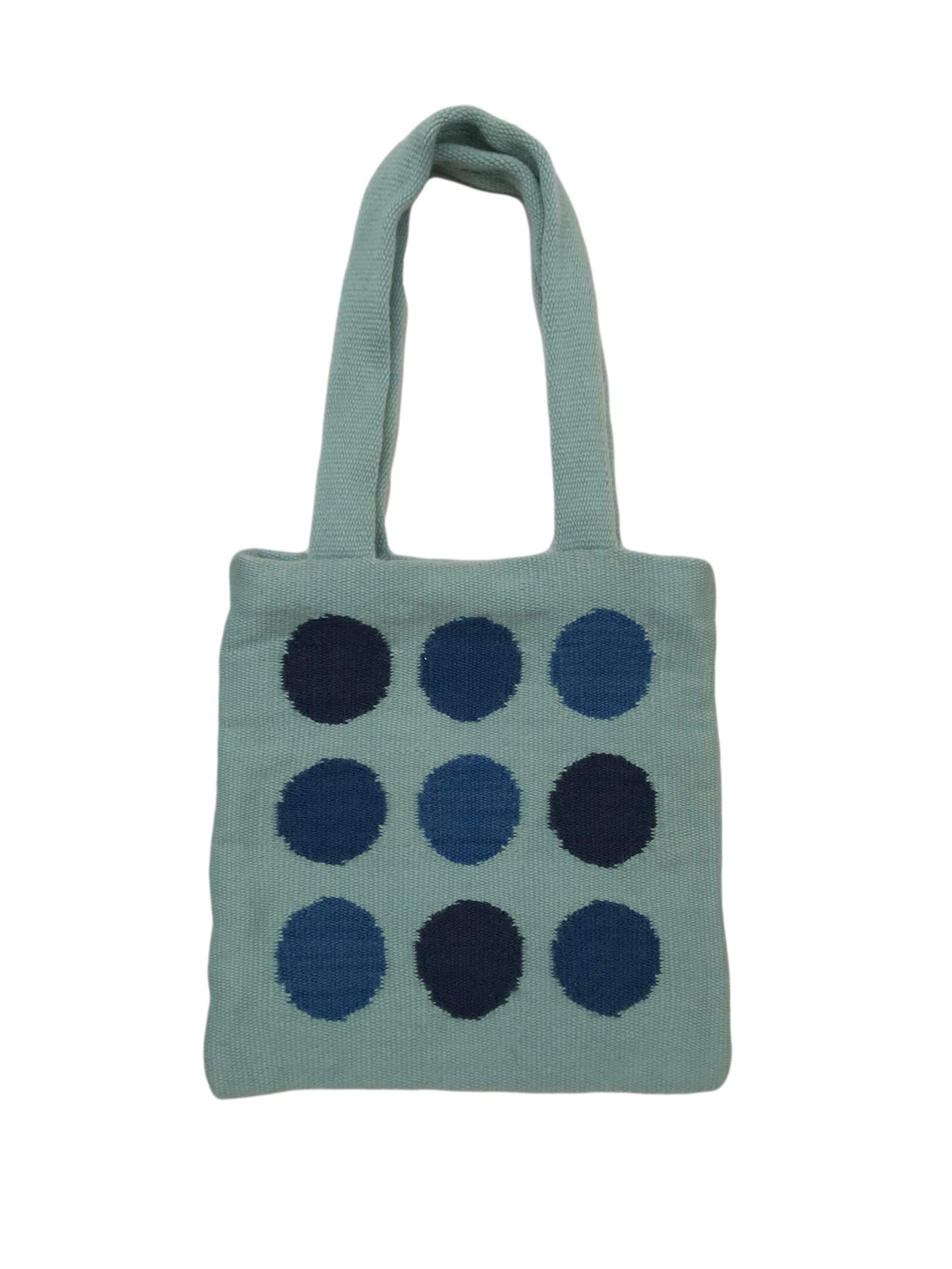 Bolso de punto celeste con doble asa, 9 maxi dots azules, lleva forro con bolsillo interior. Medidas 29x27cm