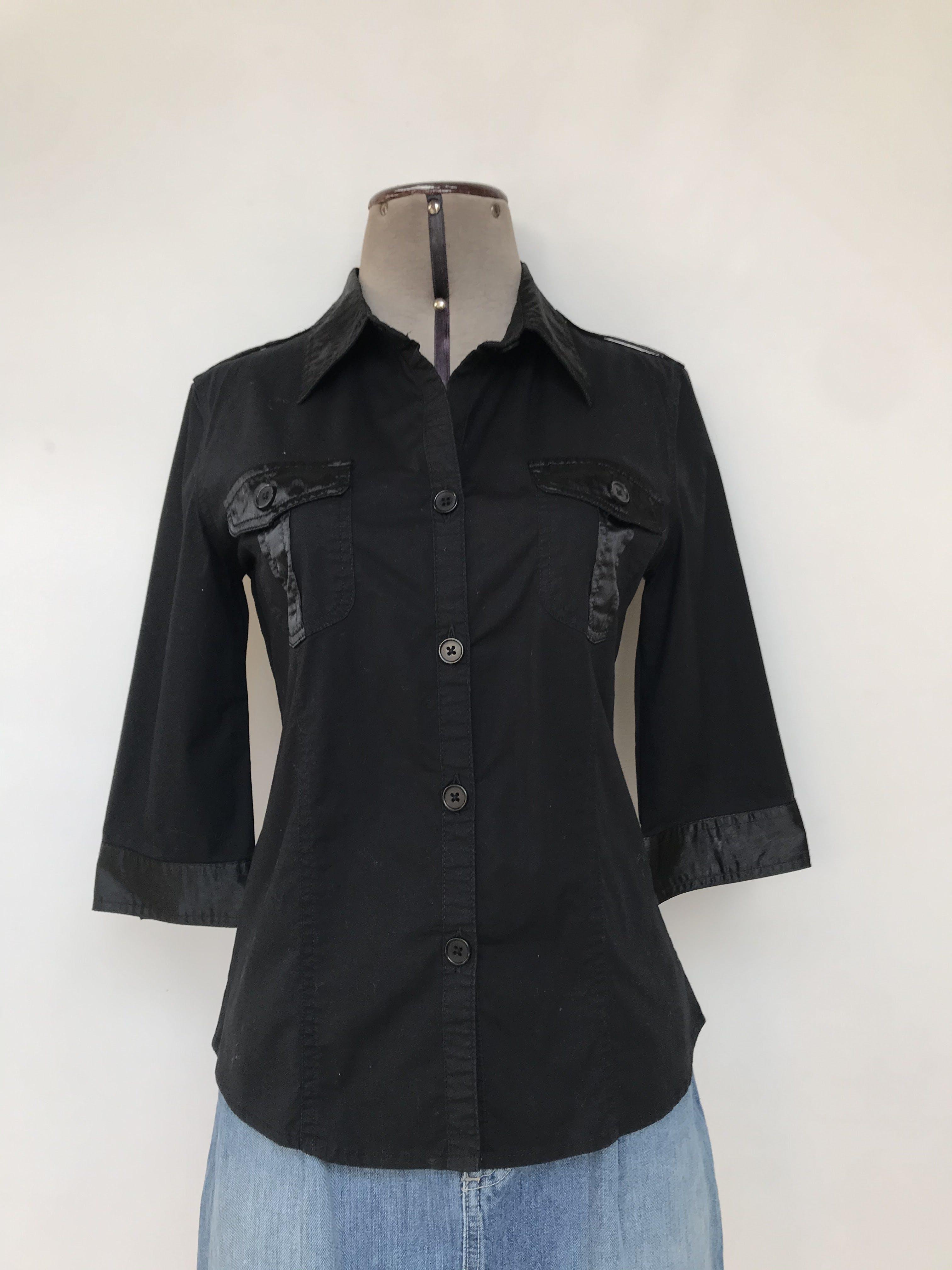 Blusa 96% algodón negro con aplicaciones de tela satinada, cuello camisero, manga 3/4 bolsillos parche en el pecho y botones al tono.Talla S