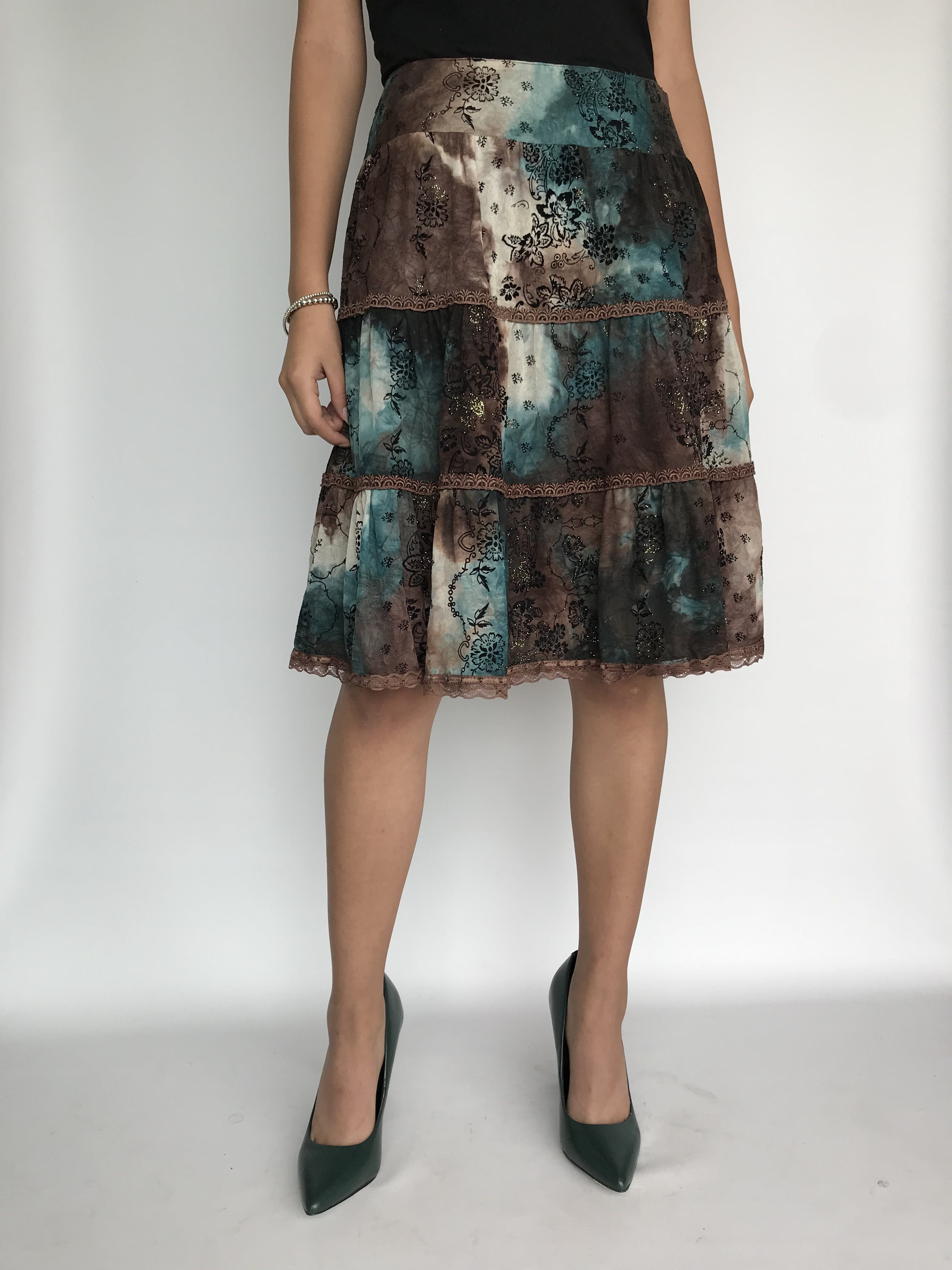 Falda Emporium a la rodilla, línea en A  sin pretina, 3 tiempos, de gasa marrón crema y verde, forrada, con estampado de flores negras en plush.   Talla M