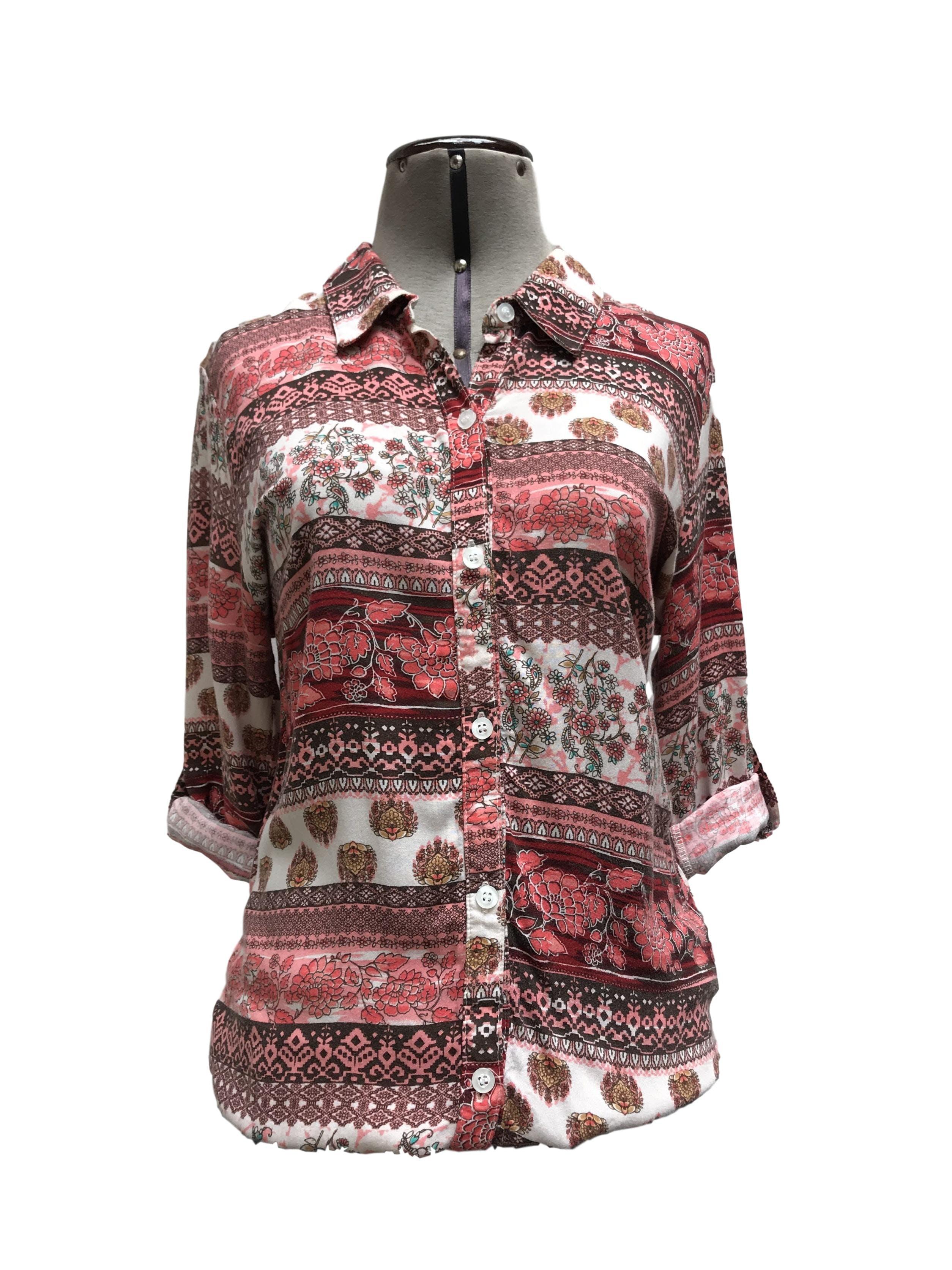 Blusa con estampado tribal en tonos coral, marrón y blanco, cuello camisero, fila de botones y elástico en las basta, manga regulable con botón Talla S (puede ser M chico)