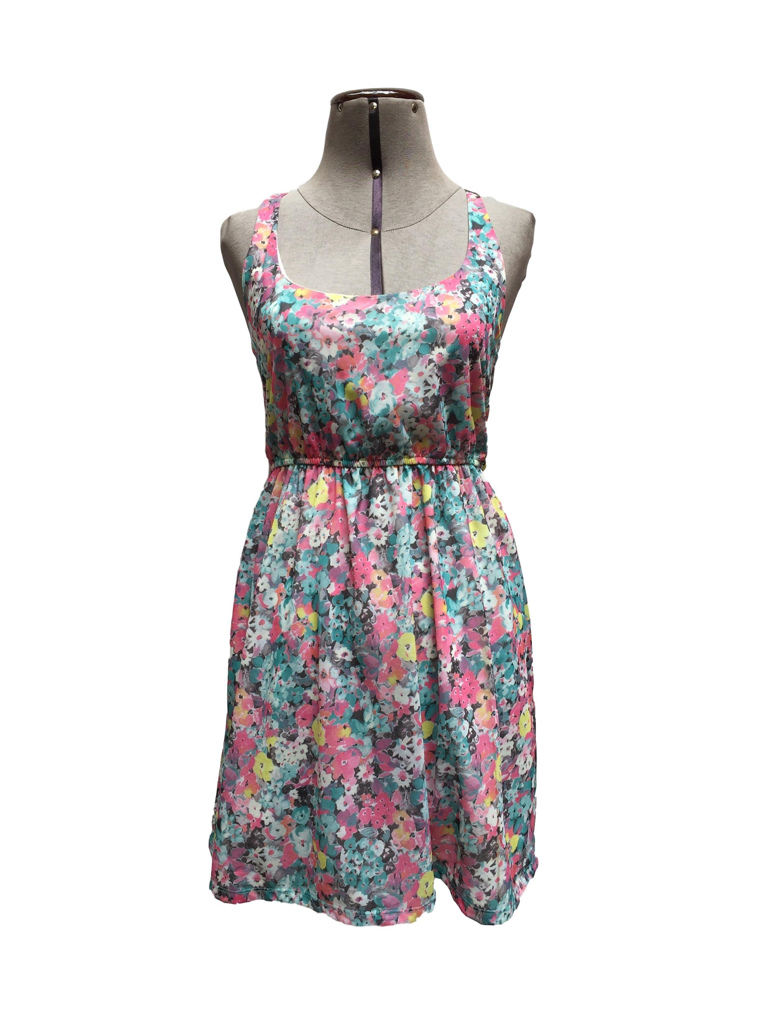 Vestido Bershka con estampado floreado de color celeste, blanco y rosado. Lleva forro, elastico en la cintura y escote con cortes en la espalda Talla S