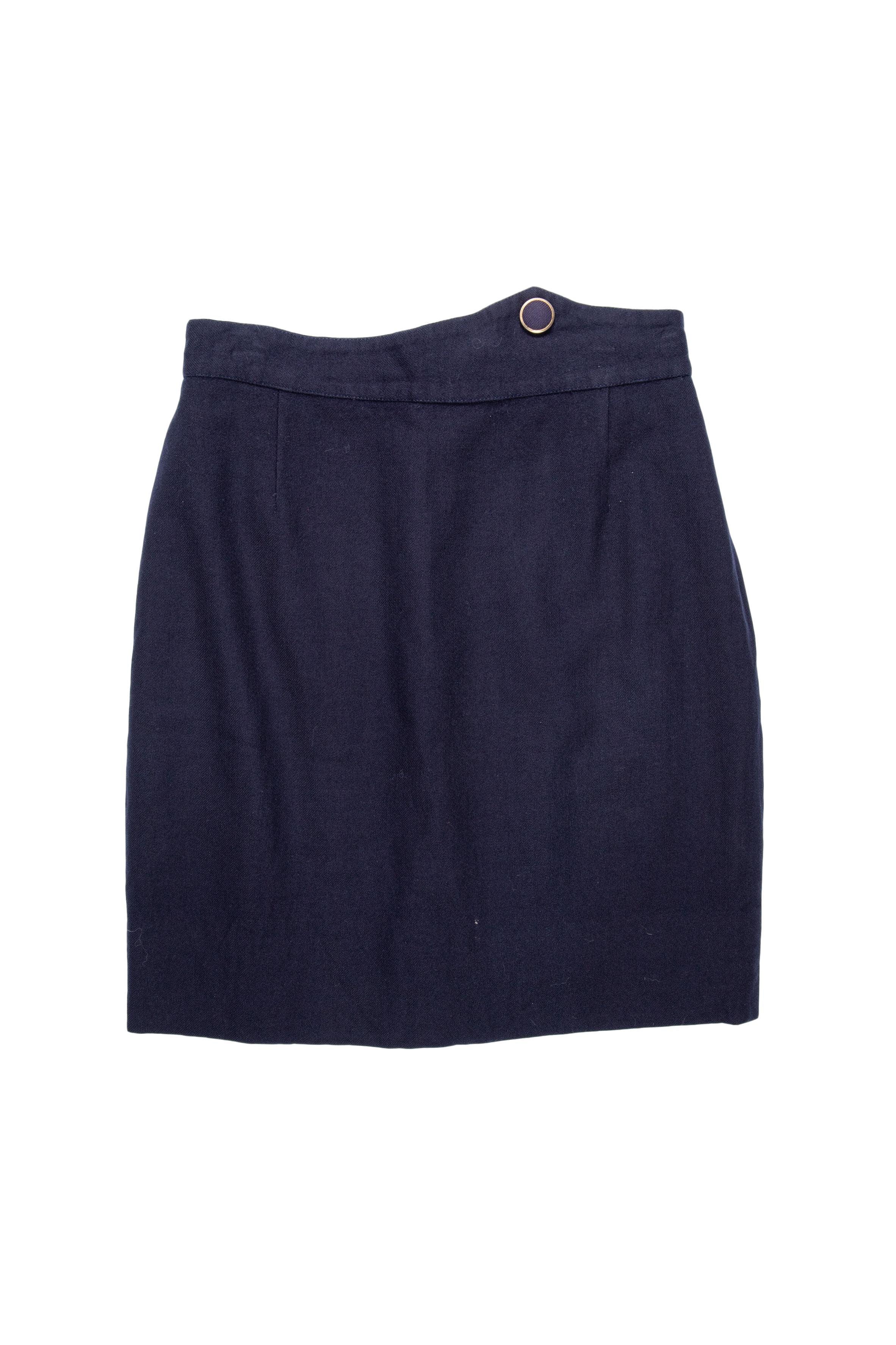 Falda de paño azul con botón forrado en la pretina, forrada y con cierre posterior. Cintura 70 cm, largo 50 cm