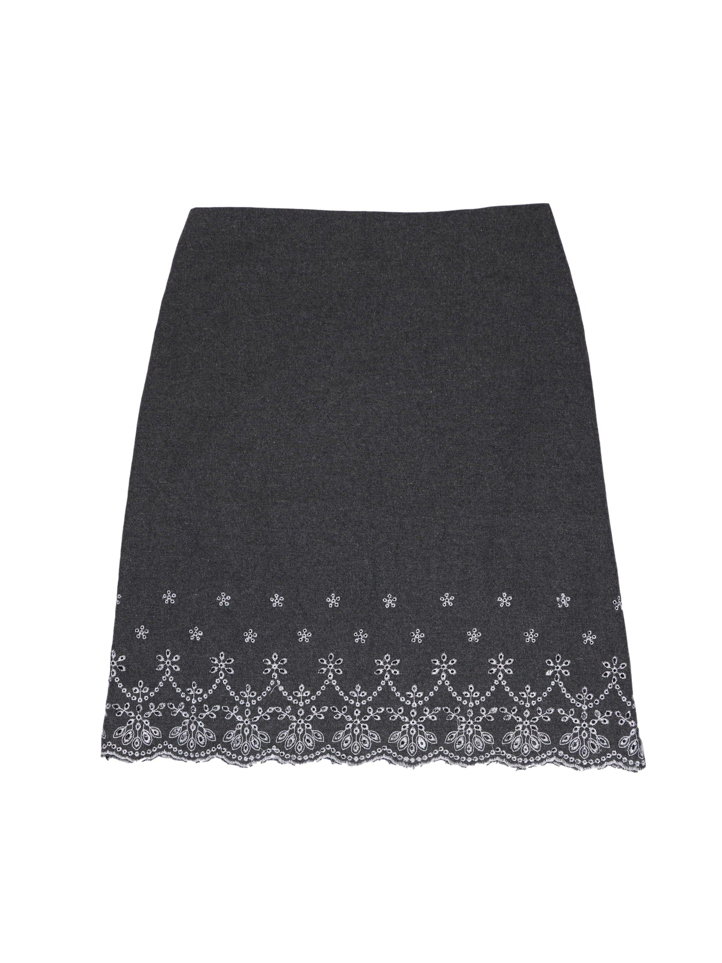 Falda gris tipo lanilla con perforaciones y bordados blancos en la basta, lleva forro y cierre lateral. Cintura 76 cm, largo 57 cm