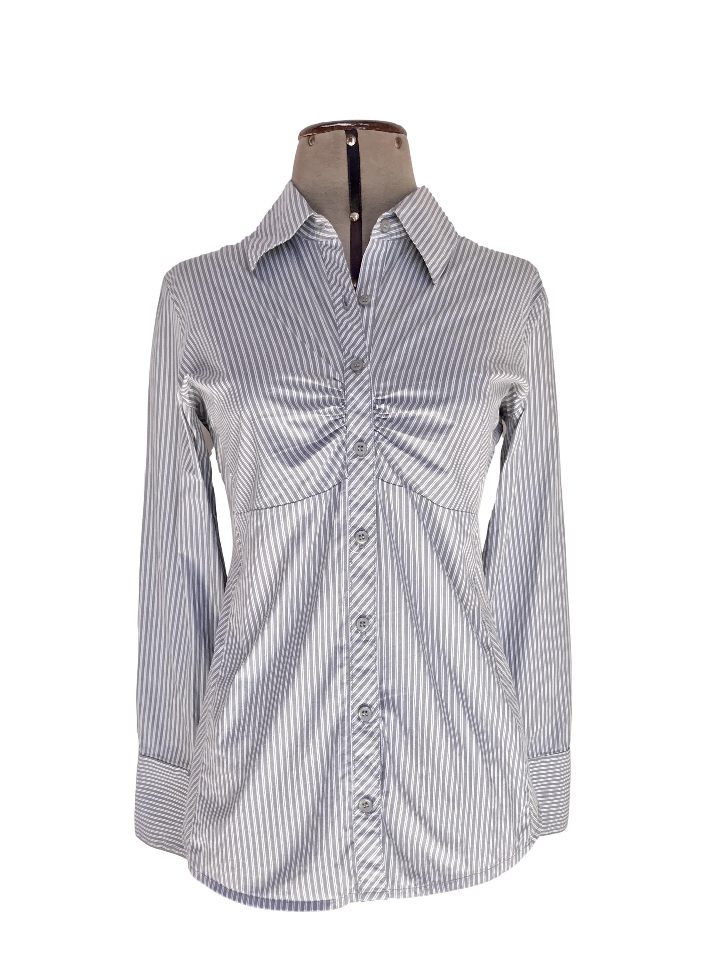 Blusa Basement a rayas blancas y plomas, cuello camisero, botones en el medio con fruncido y manga larga con puño ancho Talla M