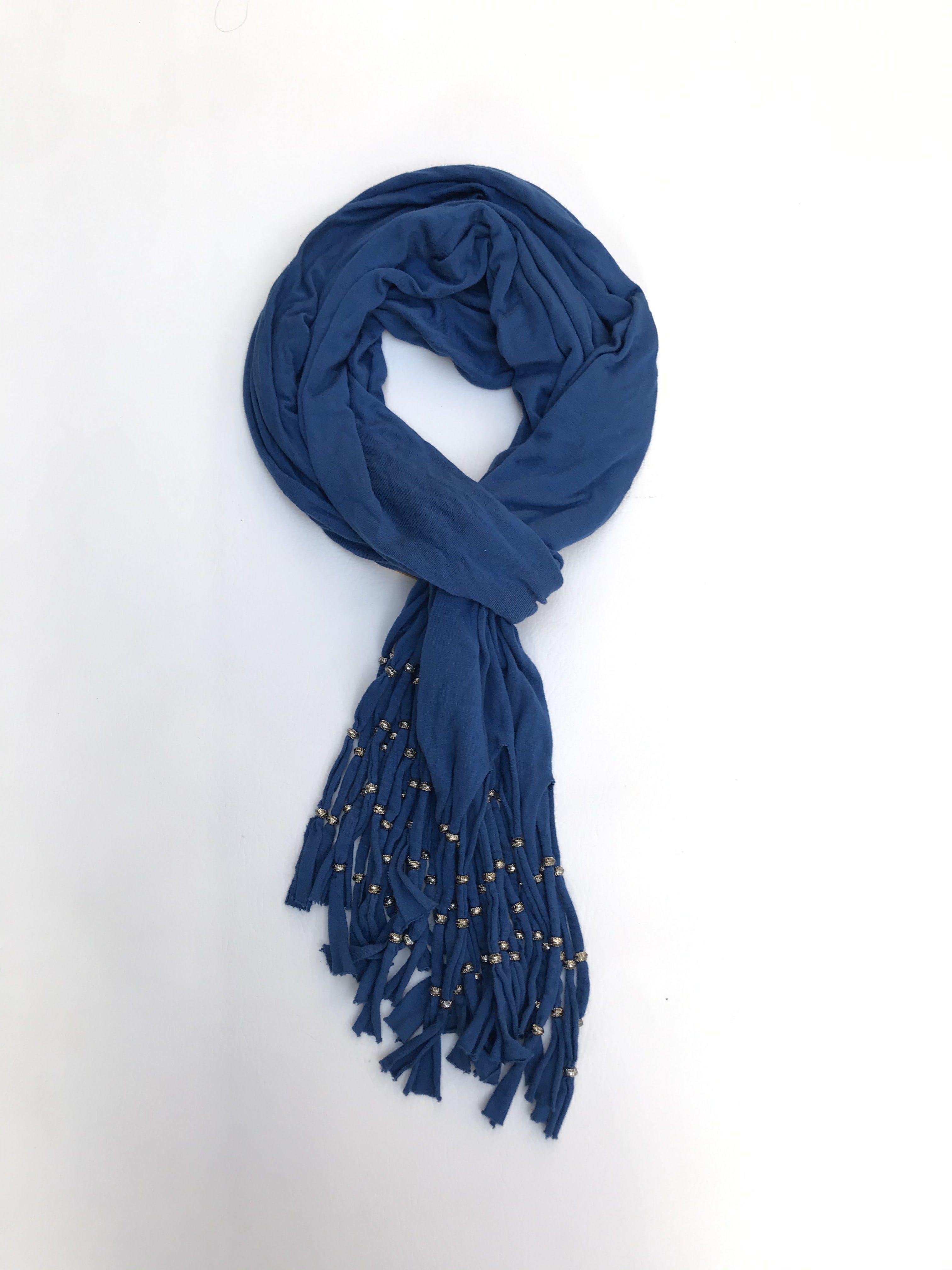 Chalina tipo algodón azul con flecos y aritos plateados. 46x190cm