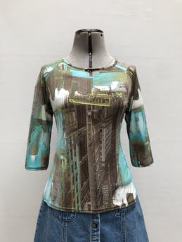 Polo de tela tipo lycra con estampado de ciudad en tonos marrones y turqueza, manga 3/4  Talla M foto 1