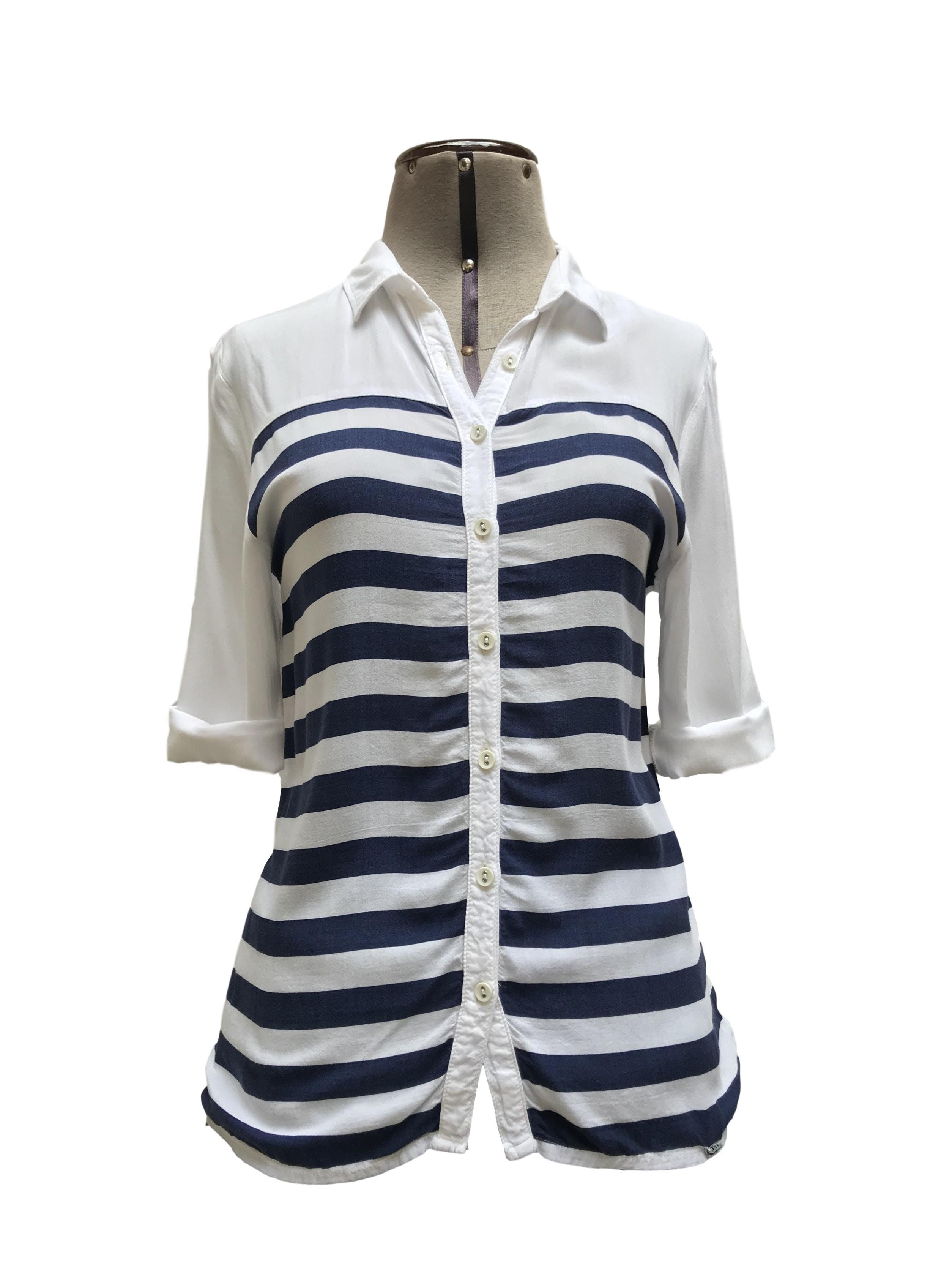 Blusa Exit blanca con estampado de franjas azules horizontales, cuello camisero y fila de botones, manga 3/4 regulable con botón Talla XS