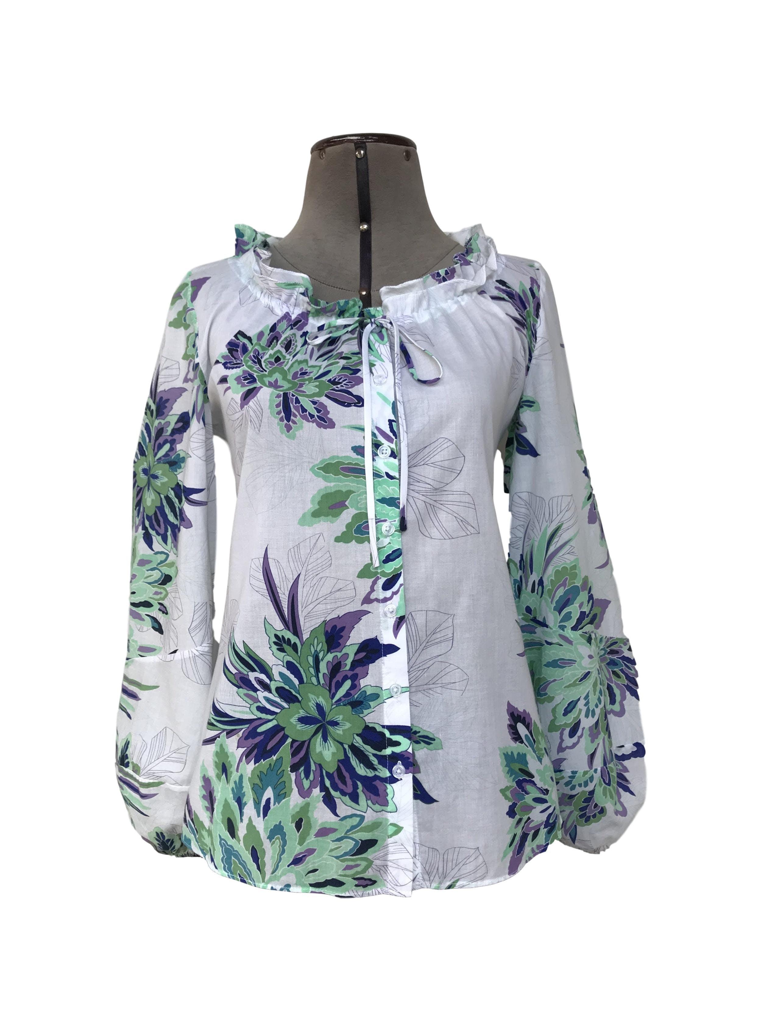 Blusa 100% algodón blanca con estampado de flores verdes y moradas, fila de botones centrales, cuello recogido con pasador y mangas bombachas con elástico en puños Talla M