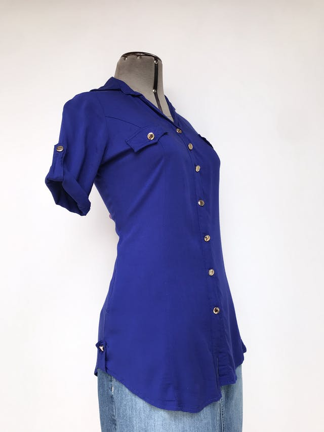 Blusa azul con botones dorados, bolsillos delanteros y mangas regulables con botón Talla S foto 2