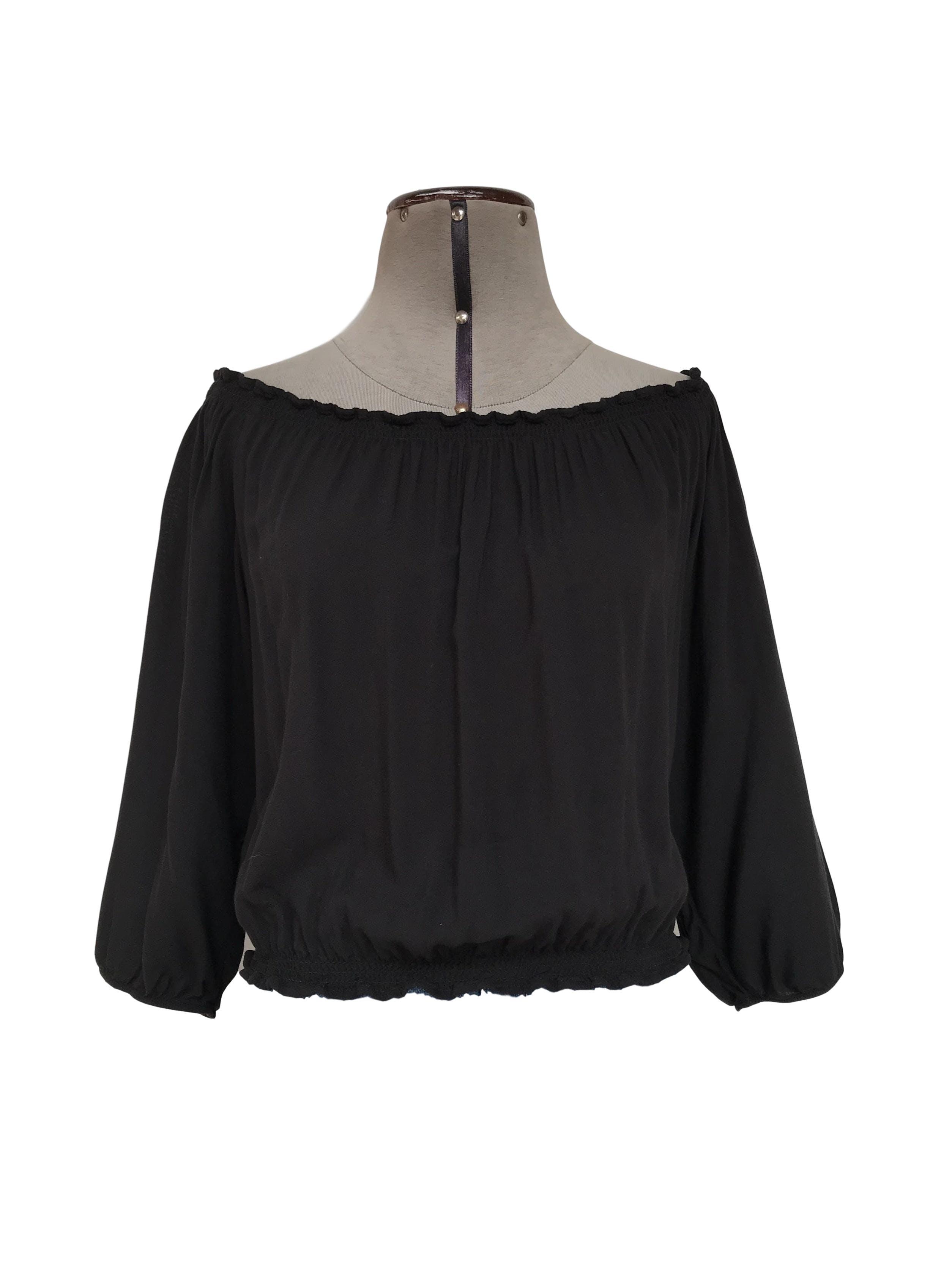 Blusa Kidsmadehere negra, off shoulder, elástico en basta y puños. Precio original S/120 Talla M