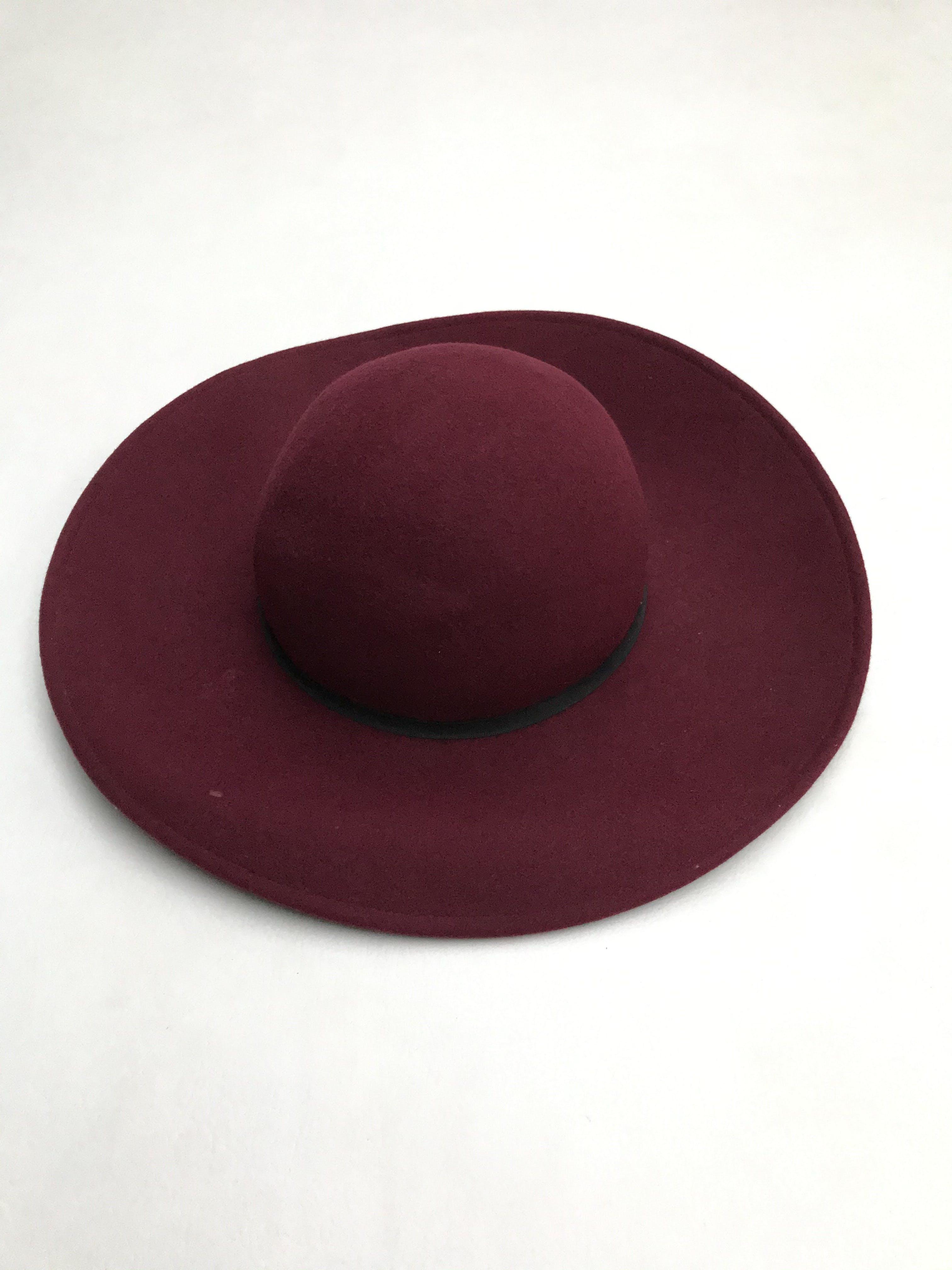 Sombrero de paño guinda con cinto negro. Tiene una marquita visible en la foto.