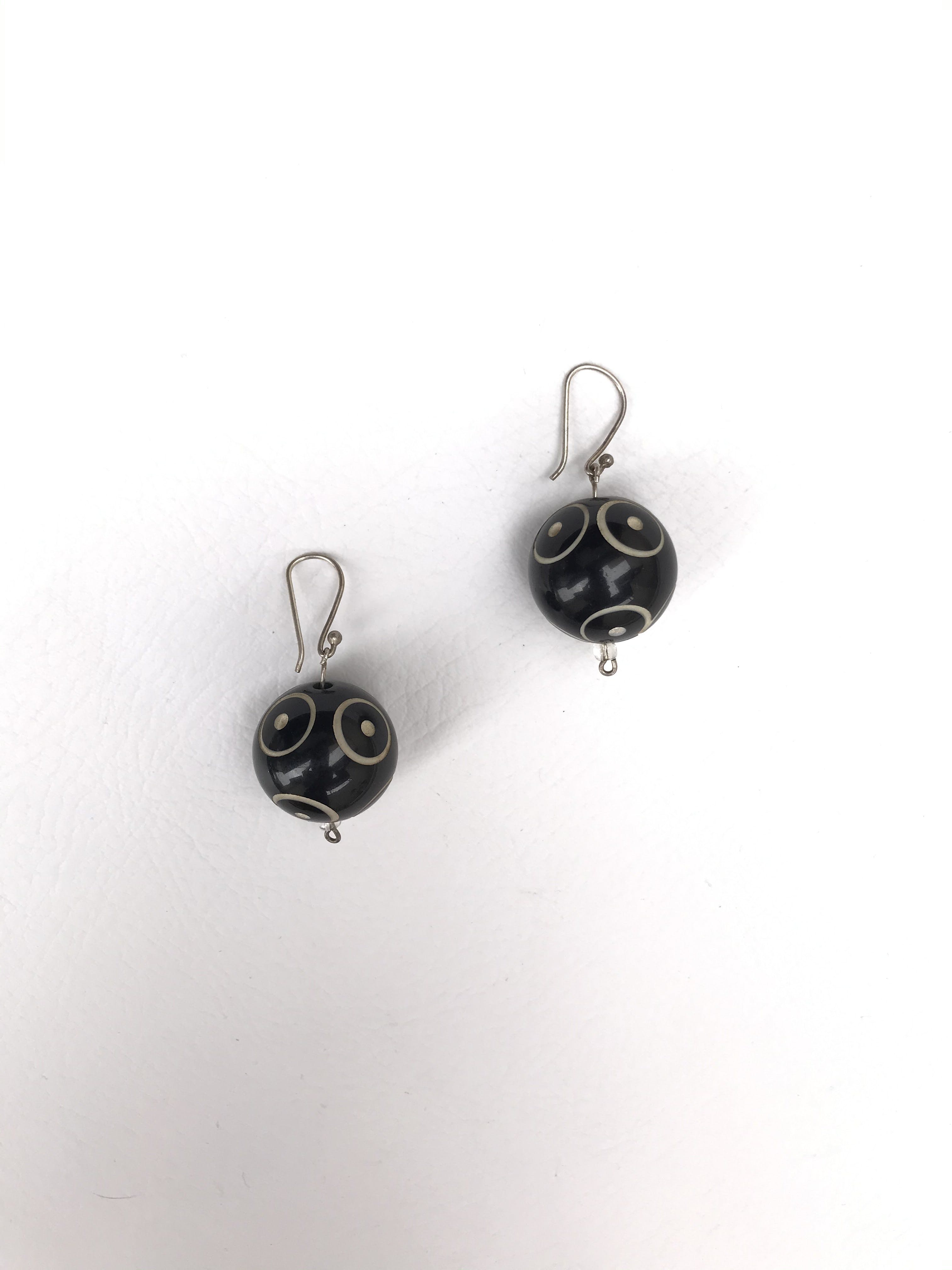 Aretes esferas negras con detalles labrados crema
