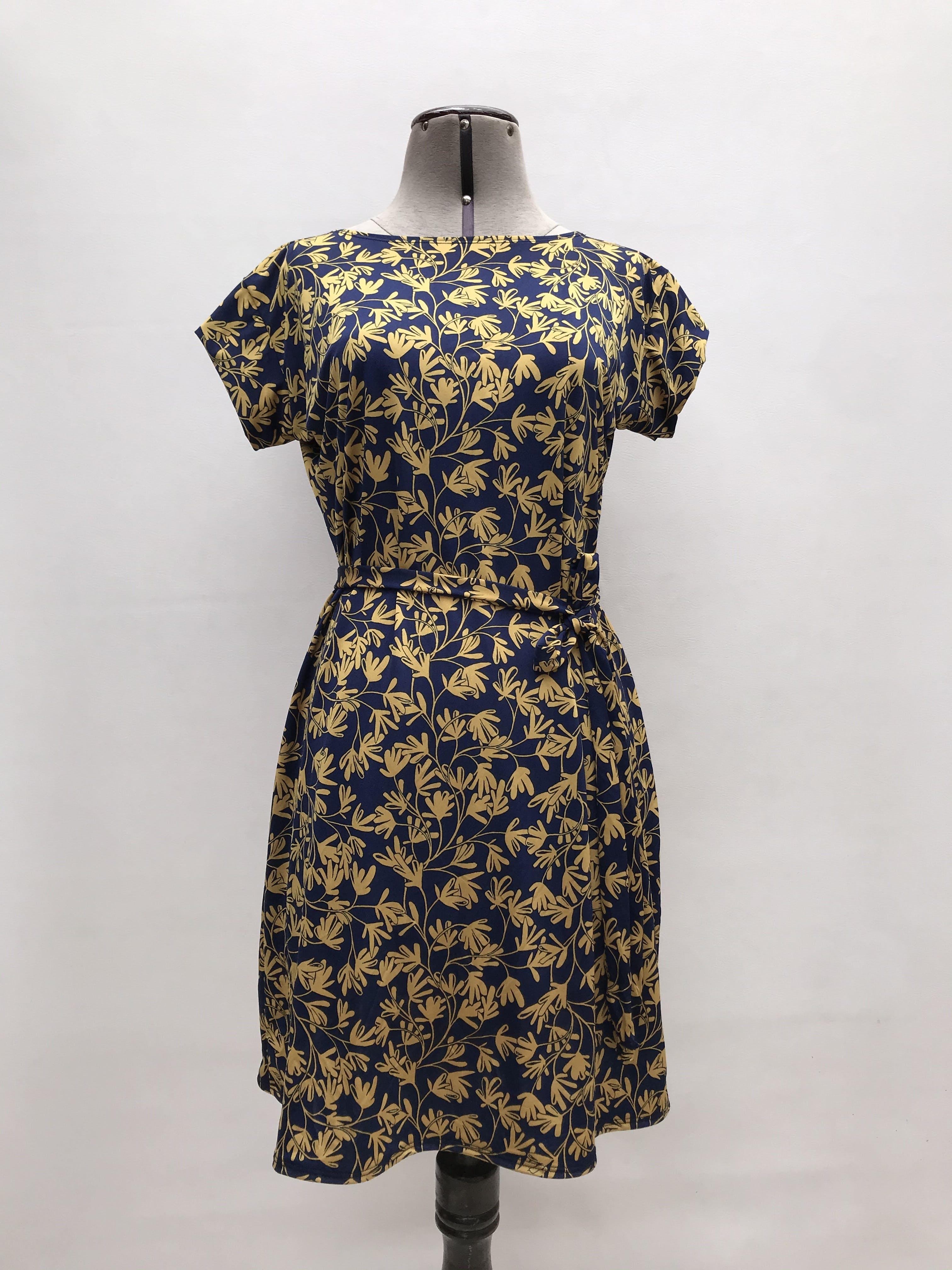 Vestido azul con estampado de hojas amarillas, tela tipo lycra, con cinto para amarrar. Largo 86cm ¡Lindo!