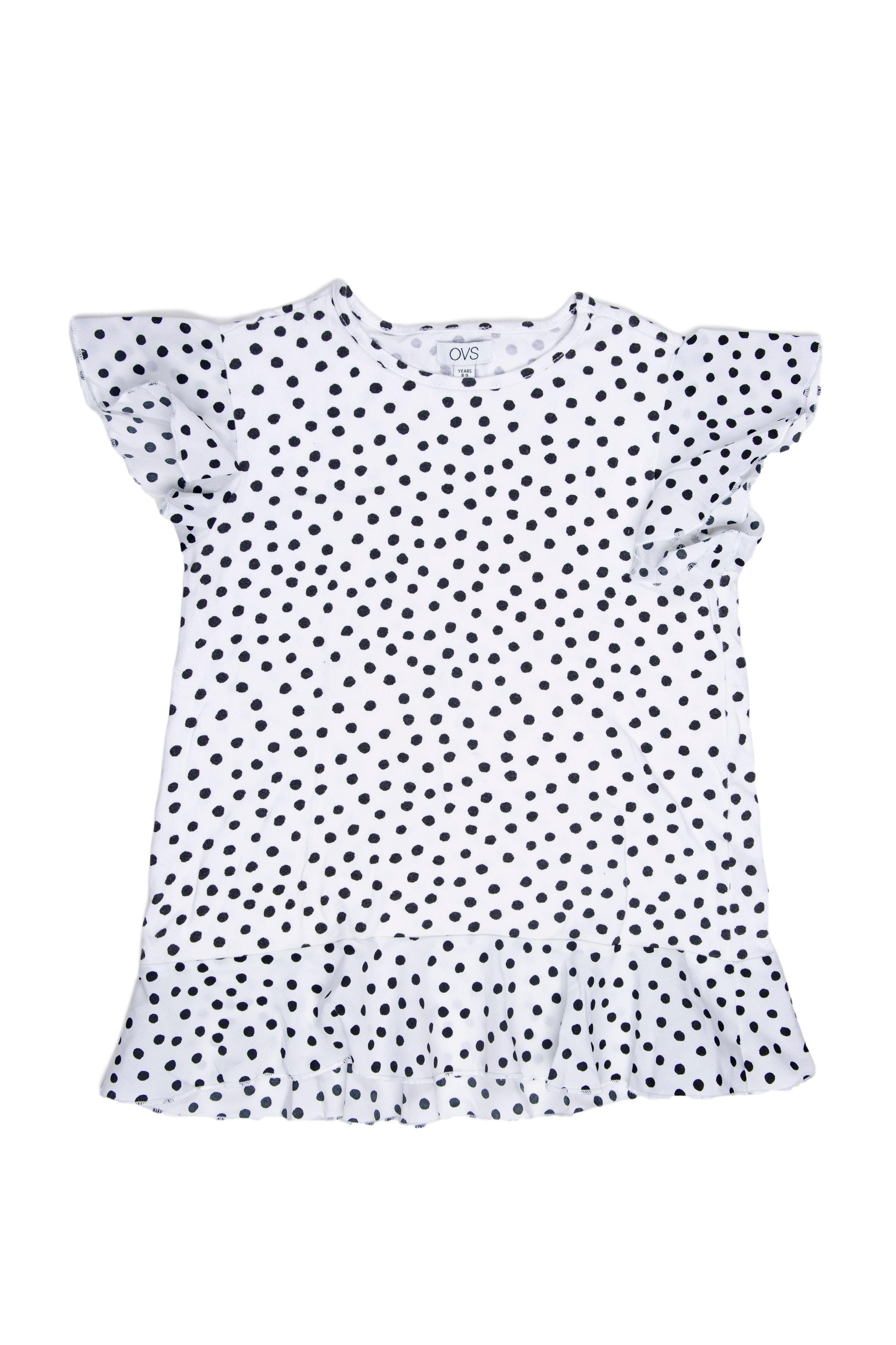 Polo blanco con puntos negros, tela elástica. Mangas y basta con blonda de tela. Talla en etiqueta: 8 - 9 años - Ovs