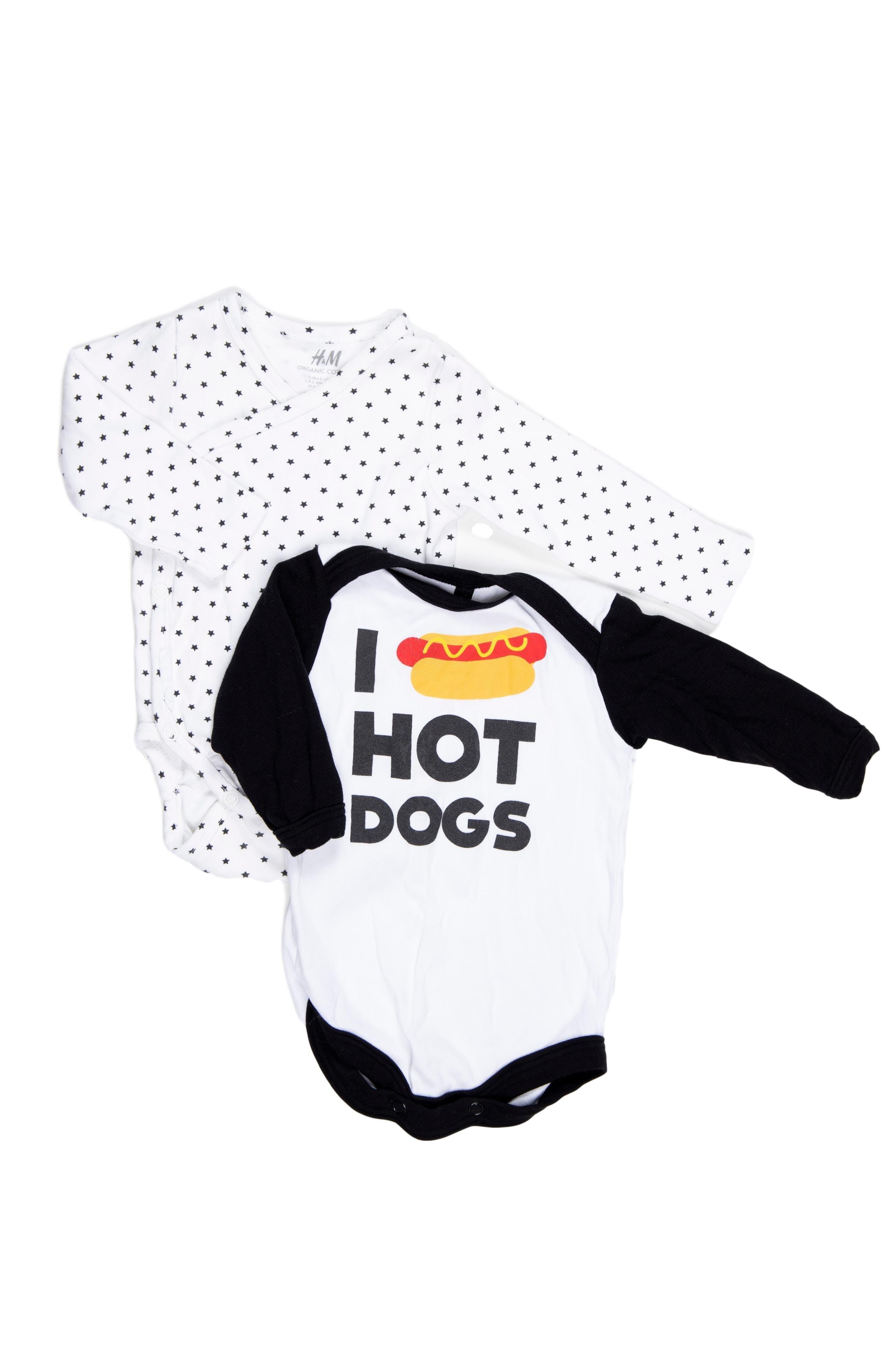 Pack de 2 bodies. Uno blanco con estrellitas negras, H&M (talla en etoqueta 2 - 4 M), otro estampado de hot dog, marca ñaña, ambos 100% algodón. - H & M