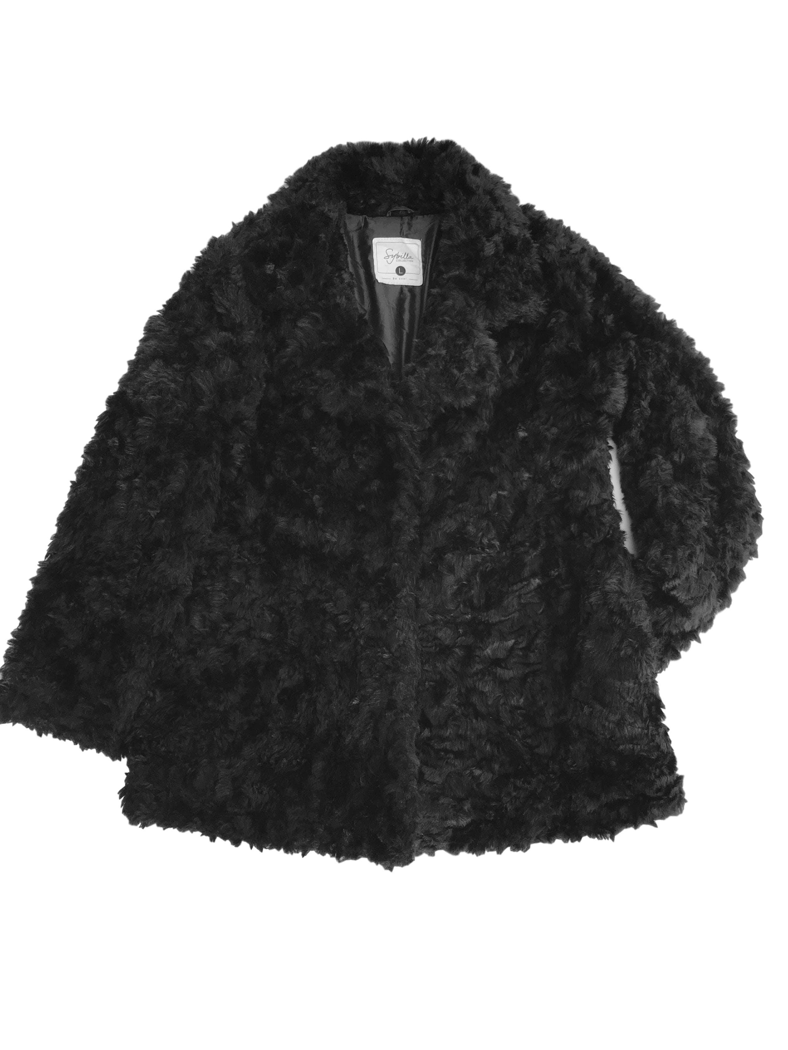 Abrigo de peluche negro, forrado, con bolsillos laterales y cierra con 3 broches. Largo bajo la cadera. Precio original S/ 200