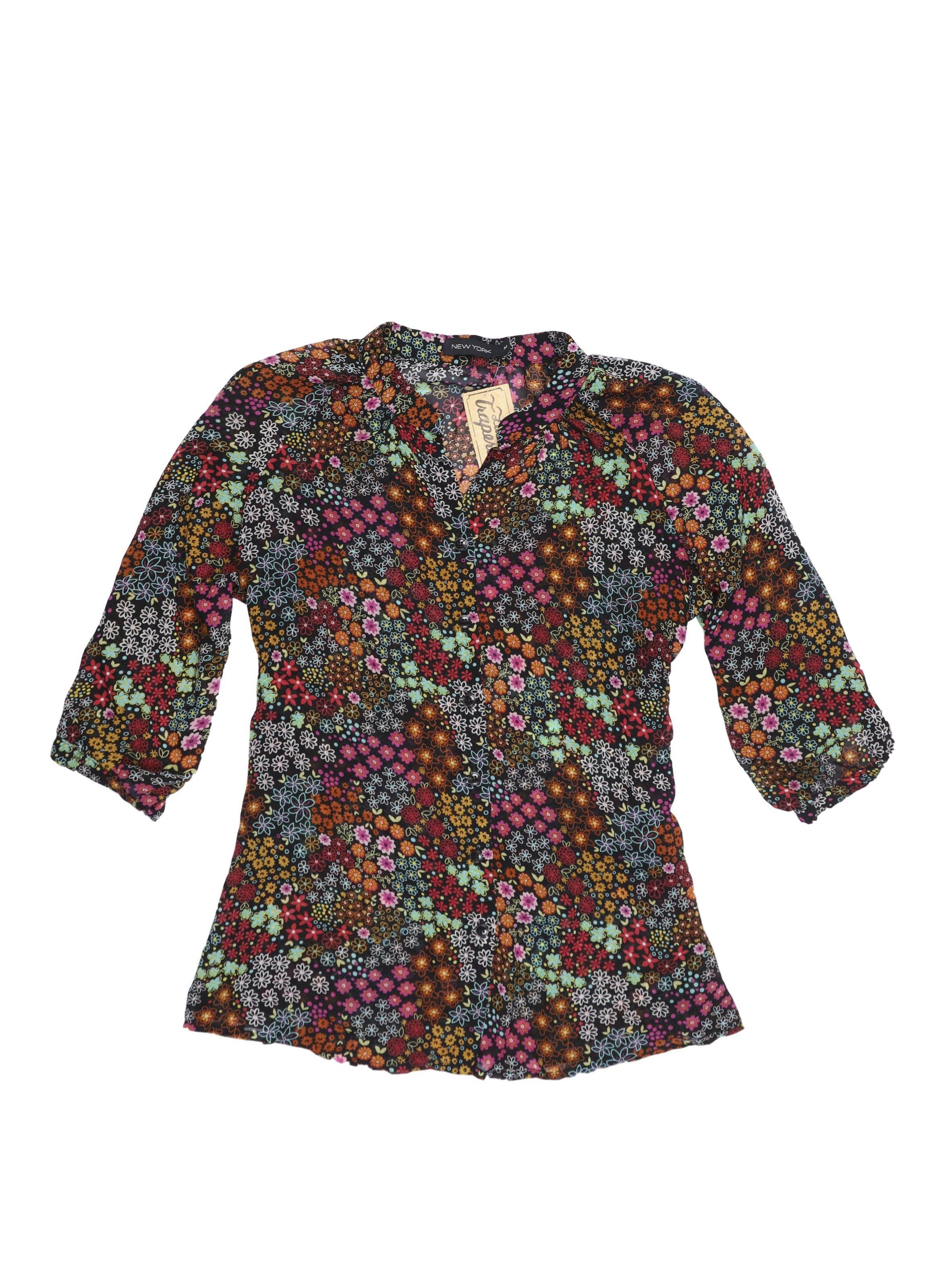 Blusa negra con estampado de flores, manga 3/4, botones al centro y tira a la cintura. Tela rica al tacto