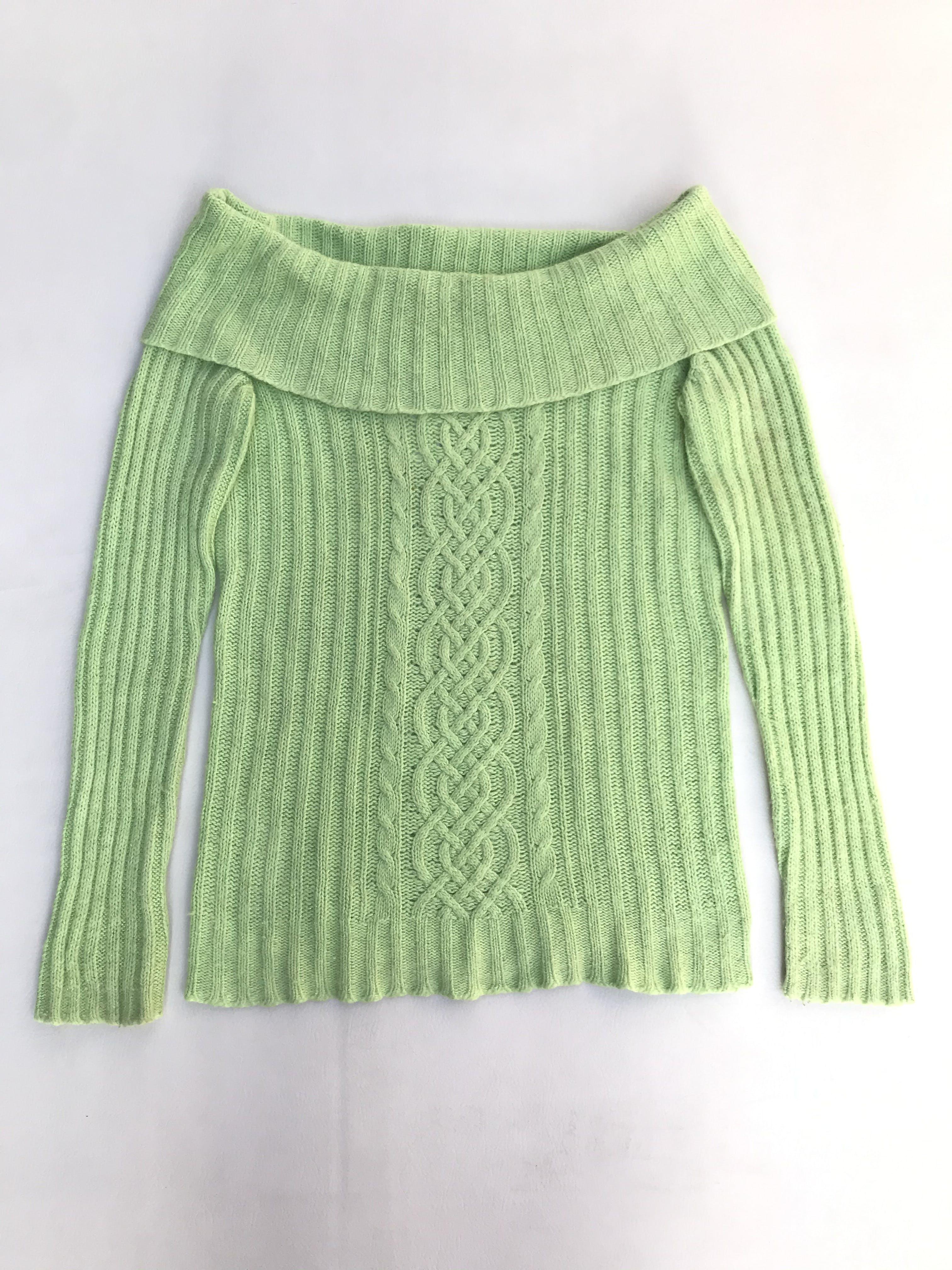 Chompa verde con hilos satinados, cuello bote, textura acanalada y trenzada. Composición ramie, nylon, angora.