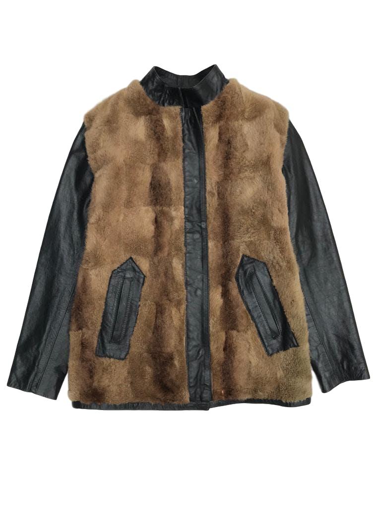 Casaca de cuero negro y pelo marrón genuinos, forrada, cuello nerú, cierra con broches y lleva bolsillos laterales. Una joya vintage para toda la vida.