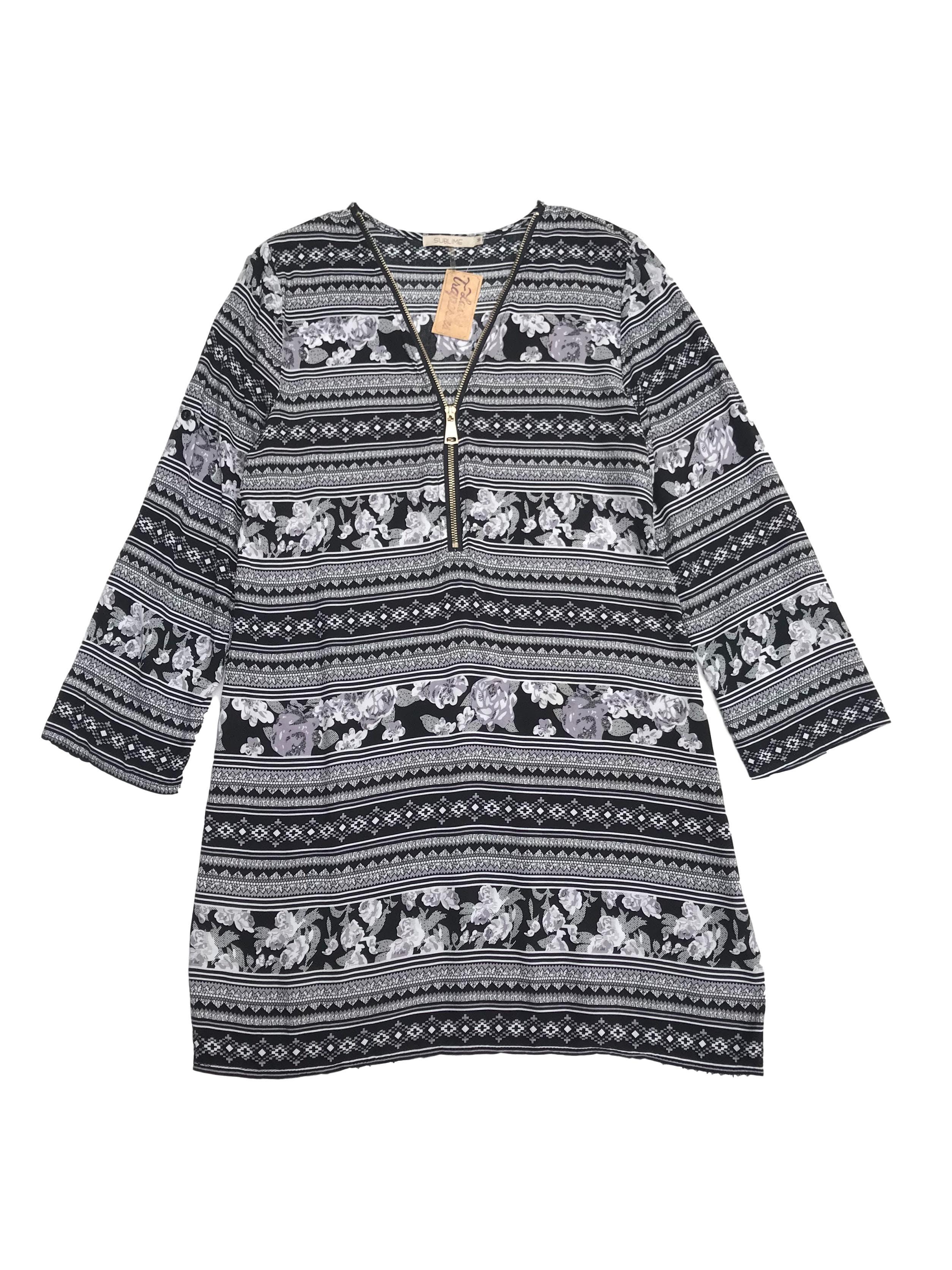 Vestido con estampado en blanco, gris y negro, cierre en el escote y mangas regulables con botón. Largo 85cm