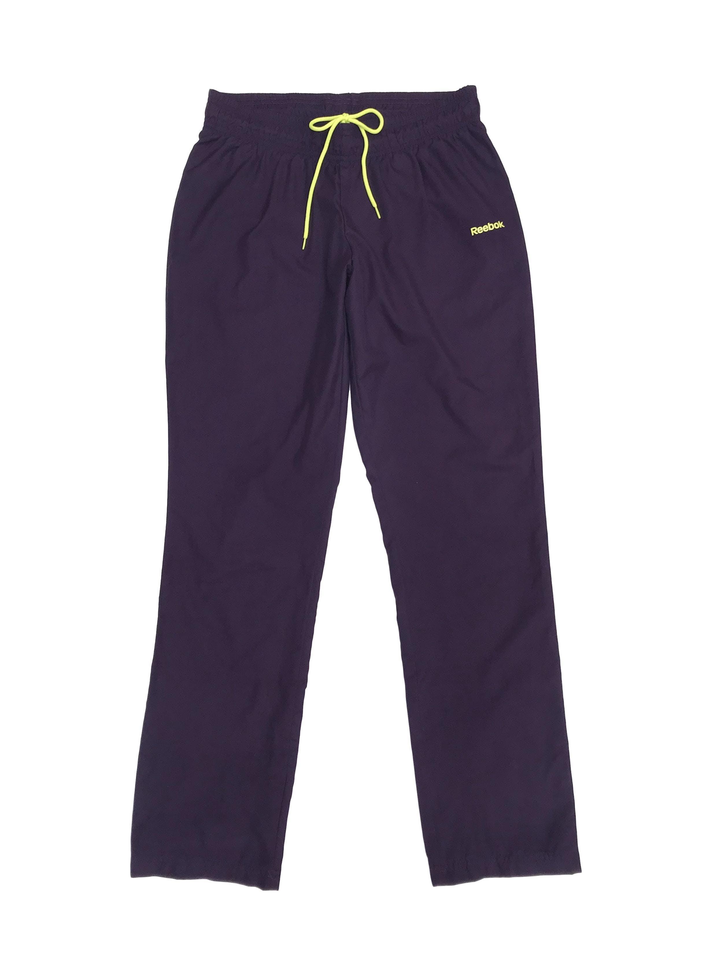 Pantalón buzo Reebok  morado con logo amarillo neón, forro malla. Precio original S/ 170