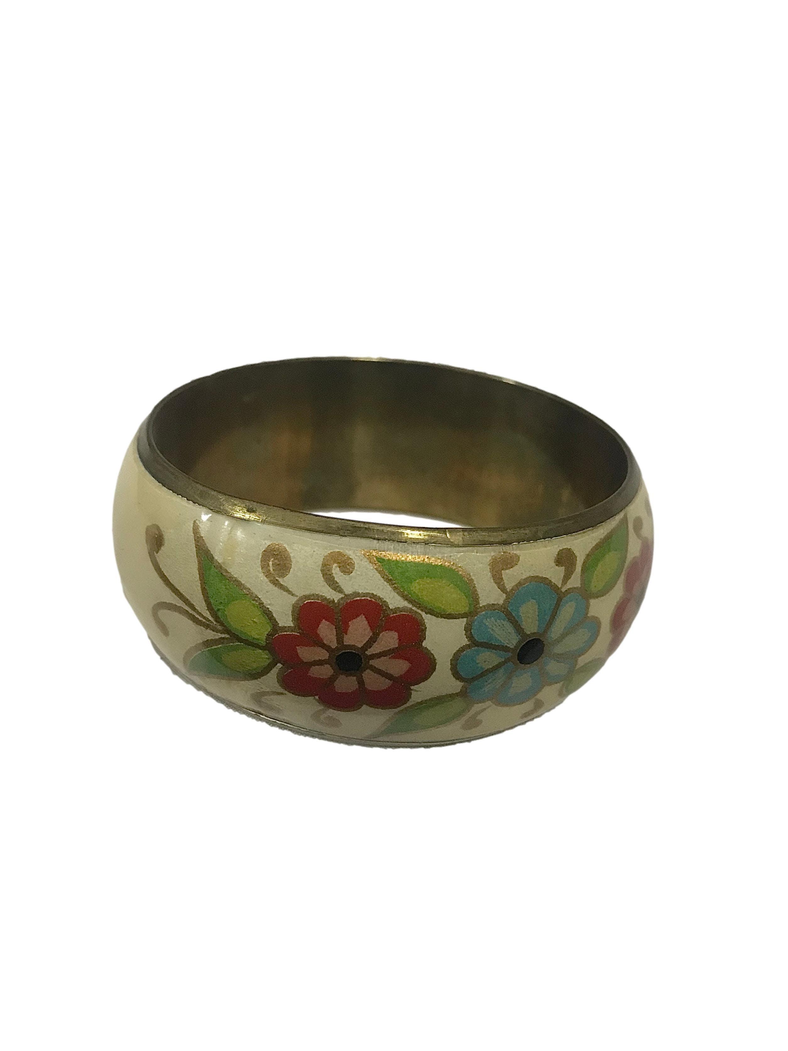 Pulsera vintage de metal con acrílico crema y flores. Circunferencia 6.5cm Ancho 2.5cm