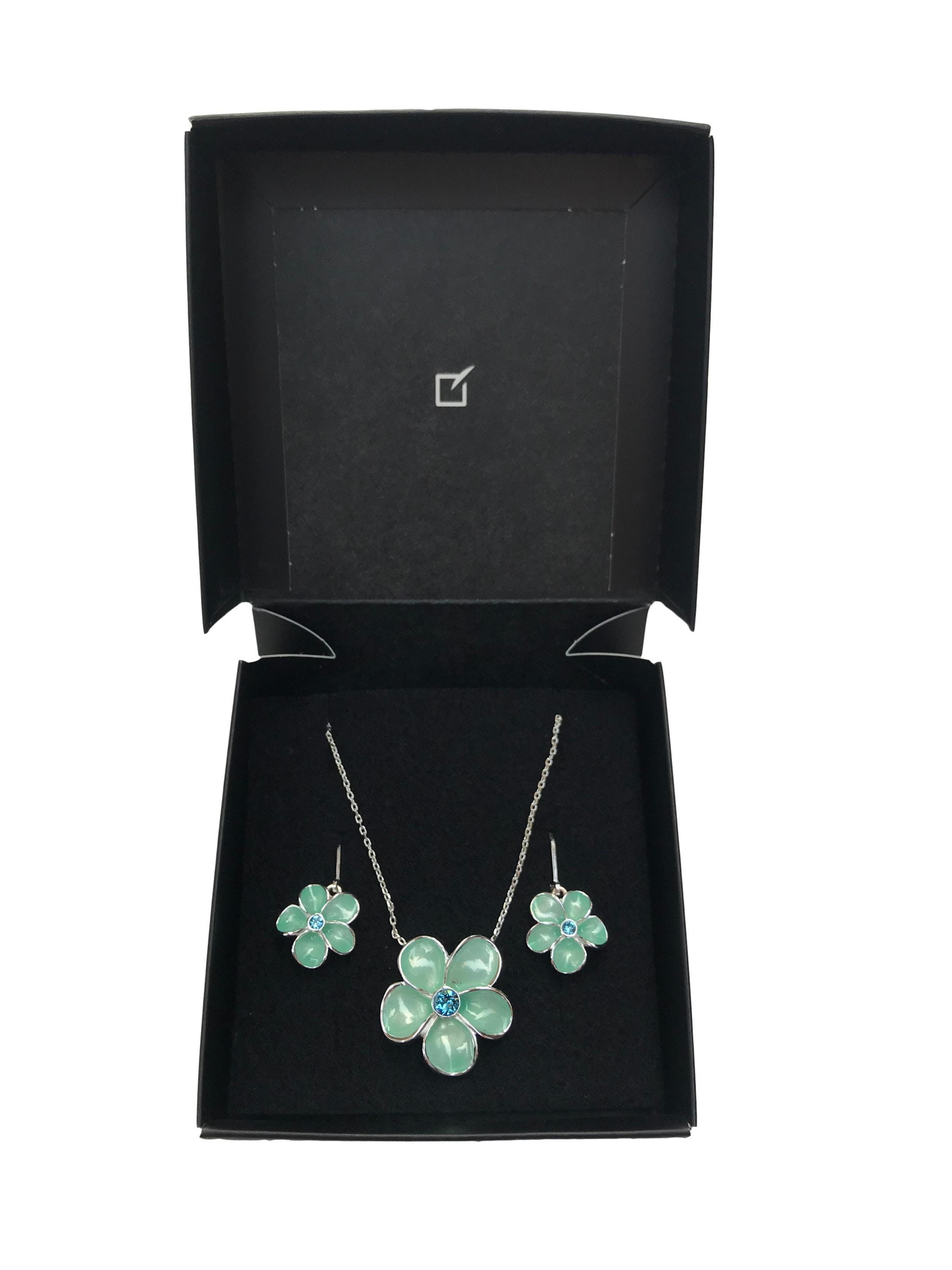 Set de collar y aretes plateados con dijes flor verde agua. Largo 40 + 7cm regulables. Vienen en caja, precio original S/ 125