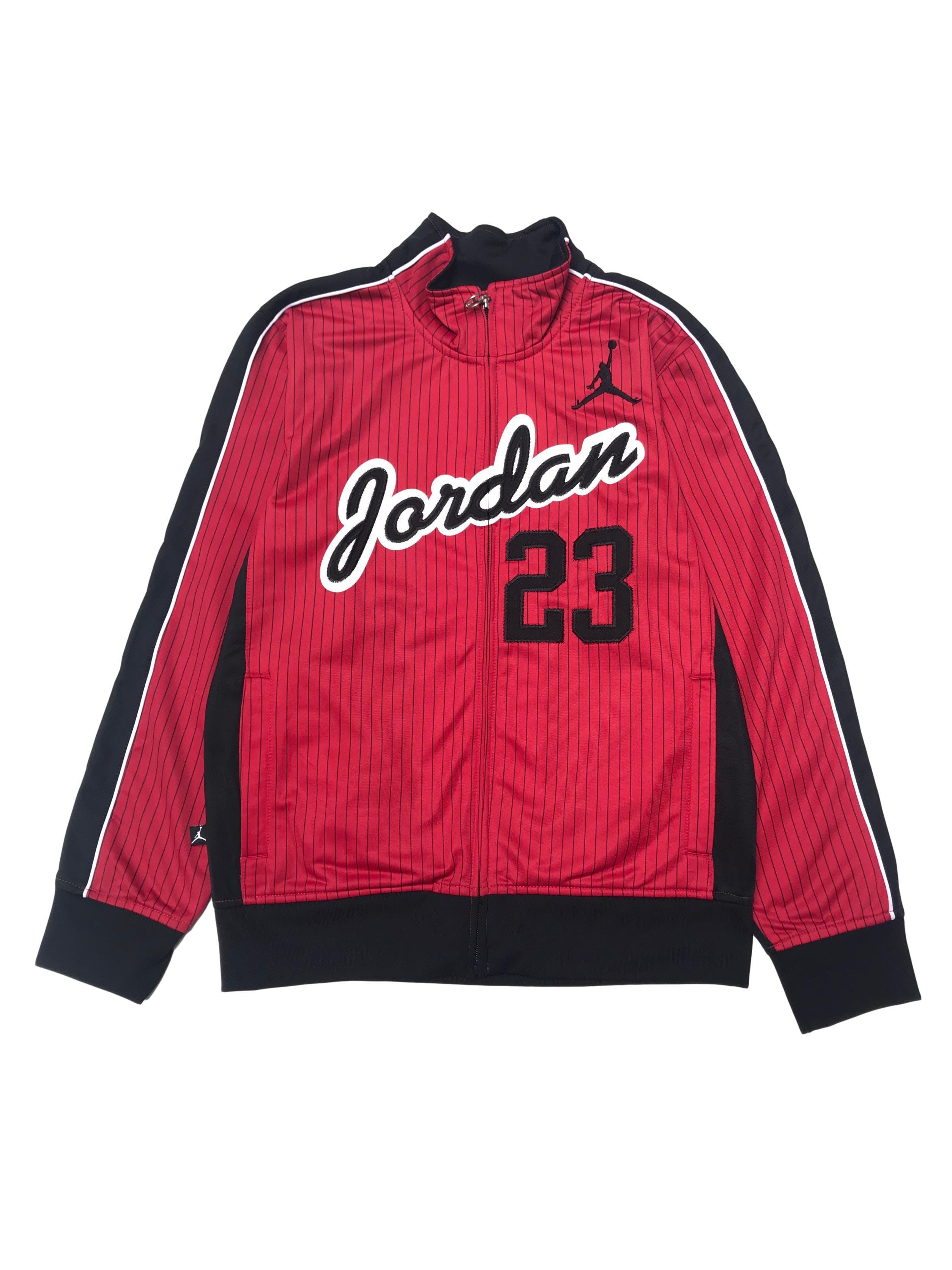 Casaca Jordan material tipo buzo deporte, posterior negro y delantero rojo con líneas y aplicaciones bordadas. Es Size Junior pero da a una S
