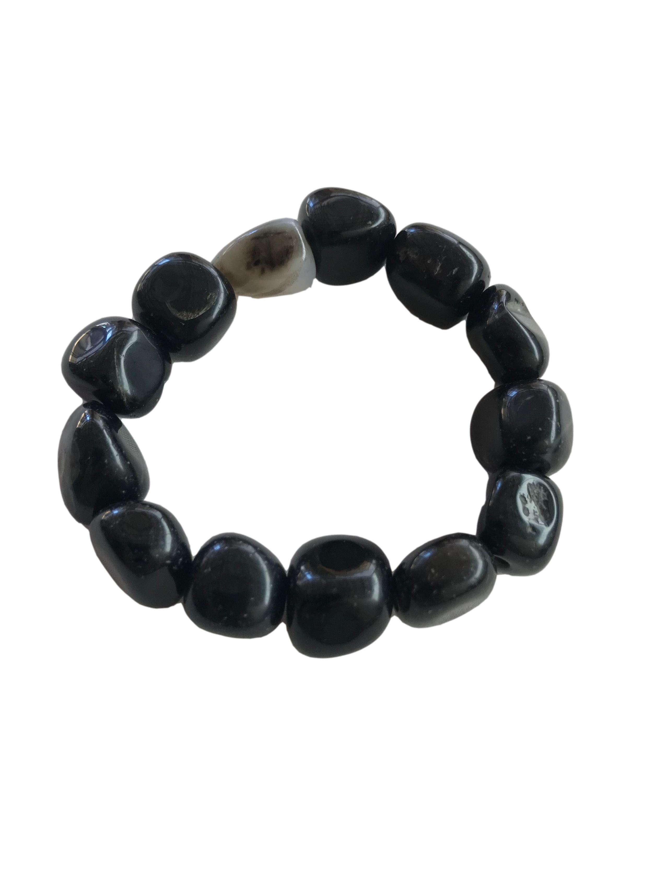 Pulsera elástica de piedras negras con una ploma. Diámetro 7 cm