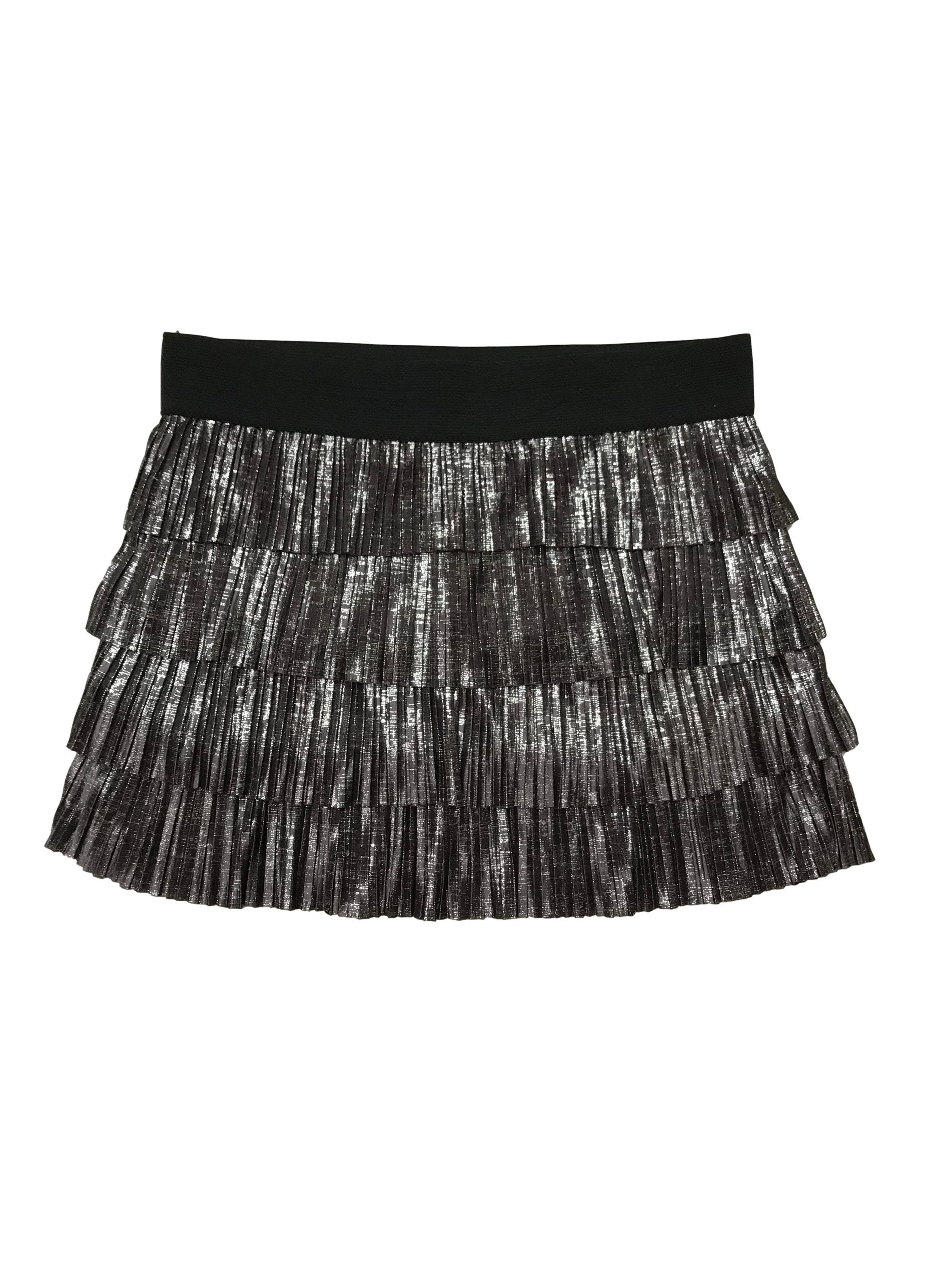 Falda de tela plisada en tiempos, tono gris brillante y pretina elástica negra. Pretina 76 cm, largo: 35 cm