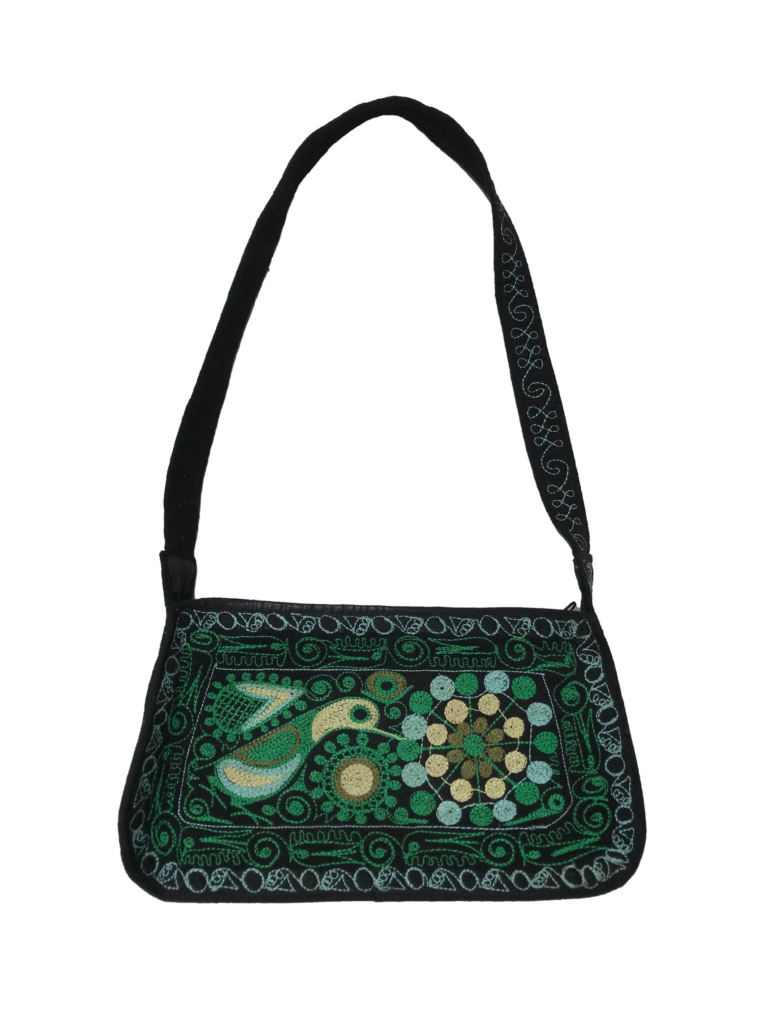 Carterita negra con bordado verde, tiene cierre y forro interno. Medidas 13x22x5cm
