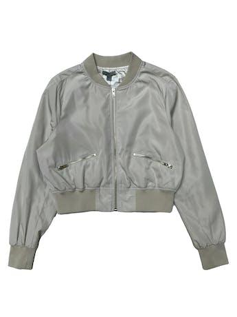 Bomber jacket corta, crema ligeramente satinada, forrada, pretina en cuello puños y basta, cierres delanteros. Busto 112cm Largo 47cm. foto 1
